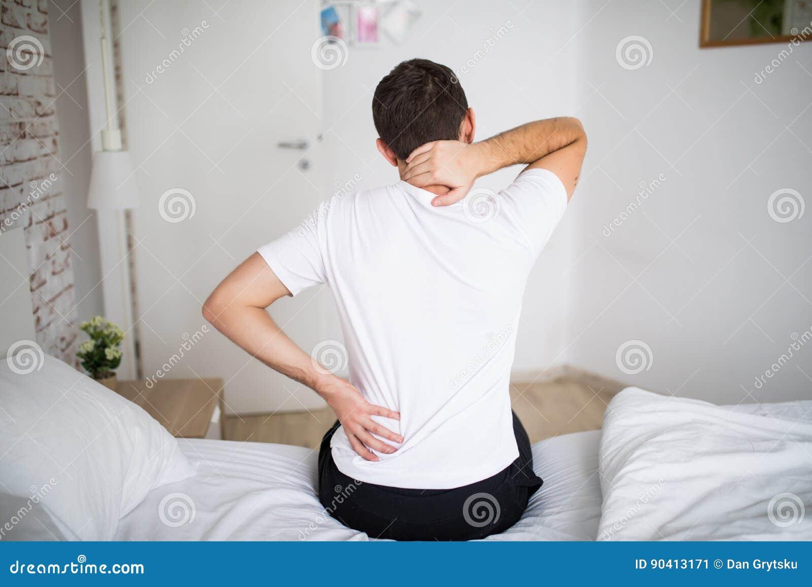 Mens die aan rugpijn thuis in de slaapkamer lijden Ongemakkelijke matras en hoofdkussenoorzaken rugpijn
