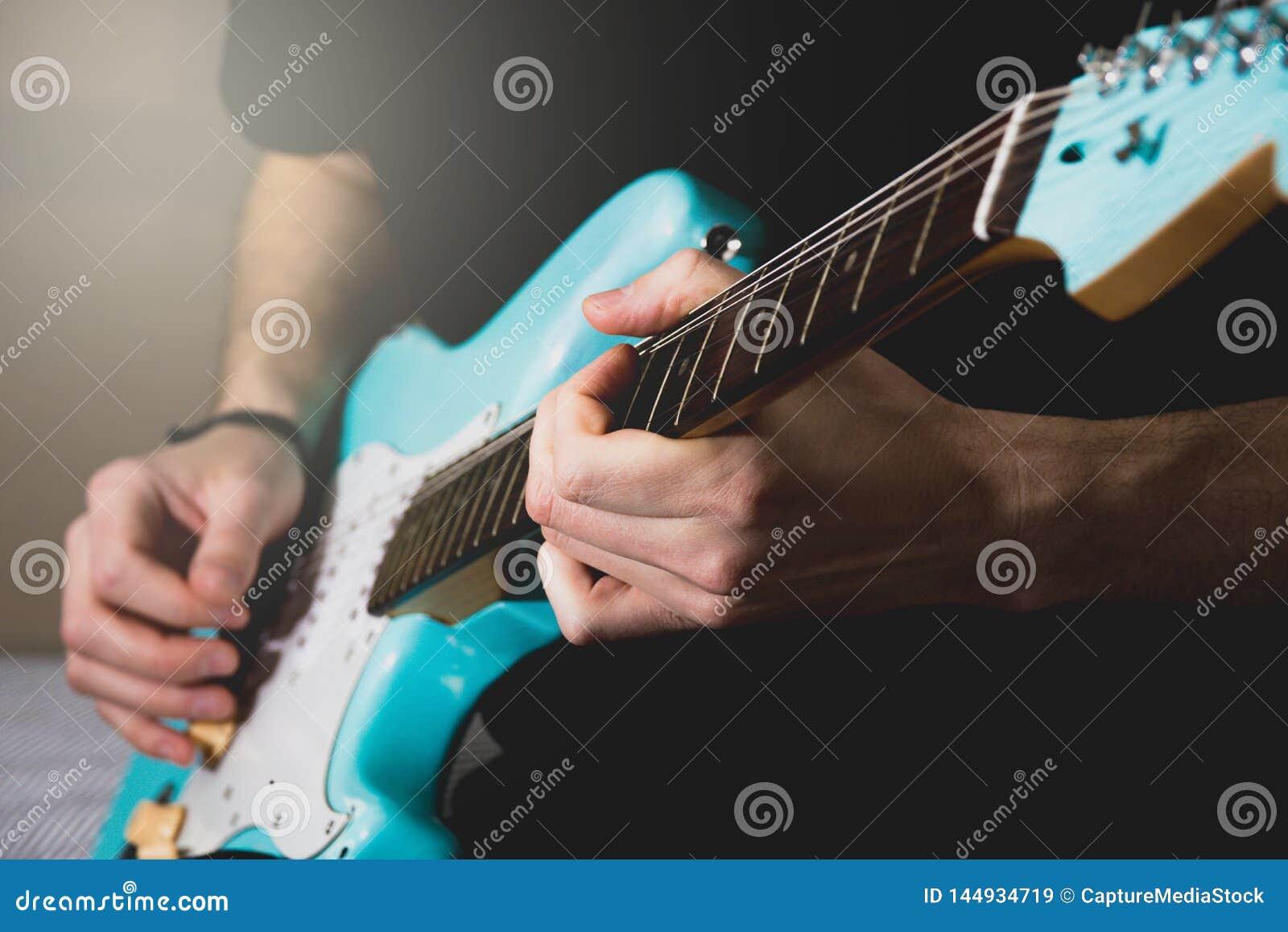 Mens die blauwe elektrische gitaar spelen dicht omhoog thuis Het praktizeren gitaar