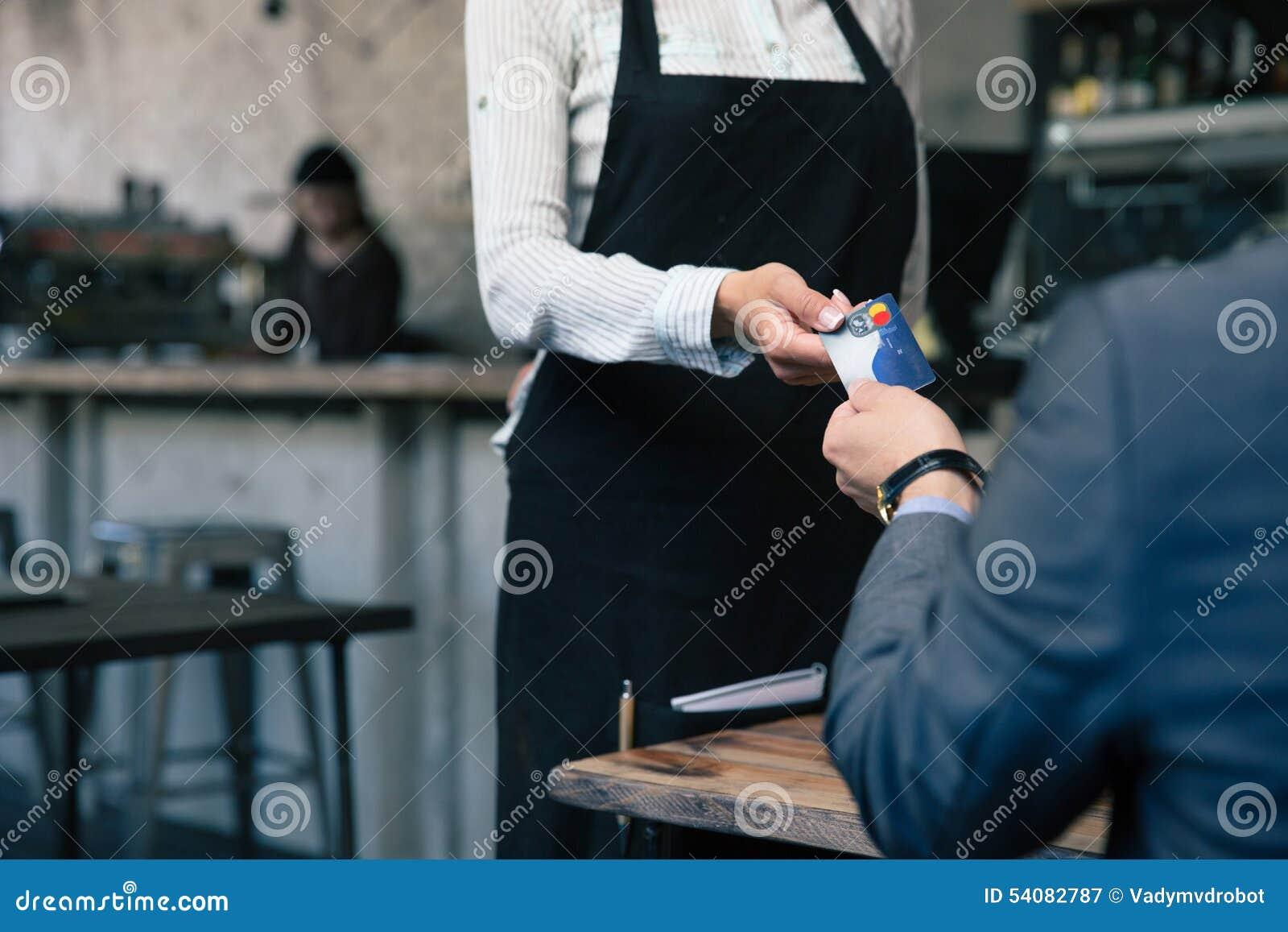 Mens die creditcard geven aan kelner in koffie