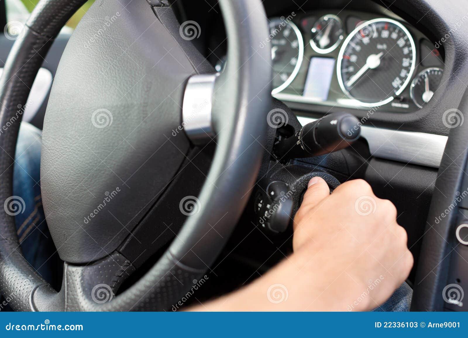 Mens die de contactsleutel van zijn auto draait