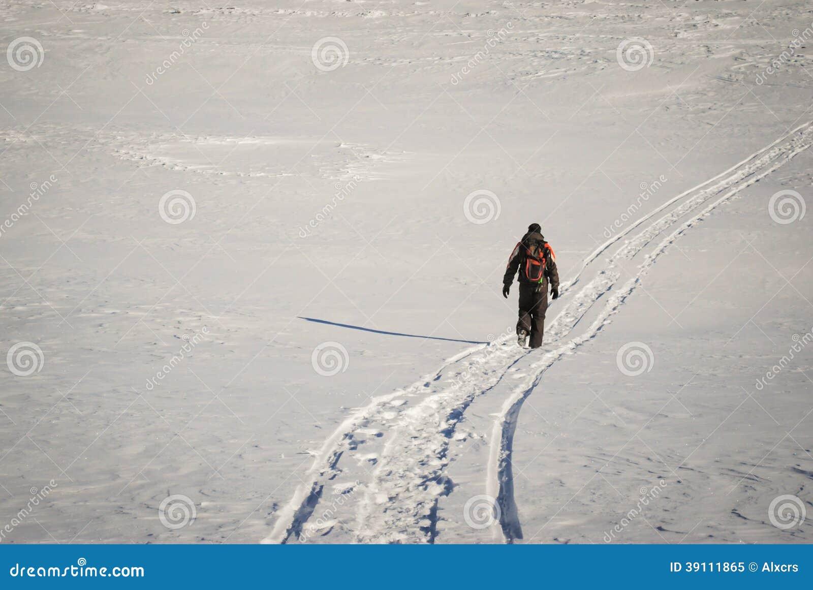 Mens die in de winter op een sneeuwsleep wandelen