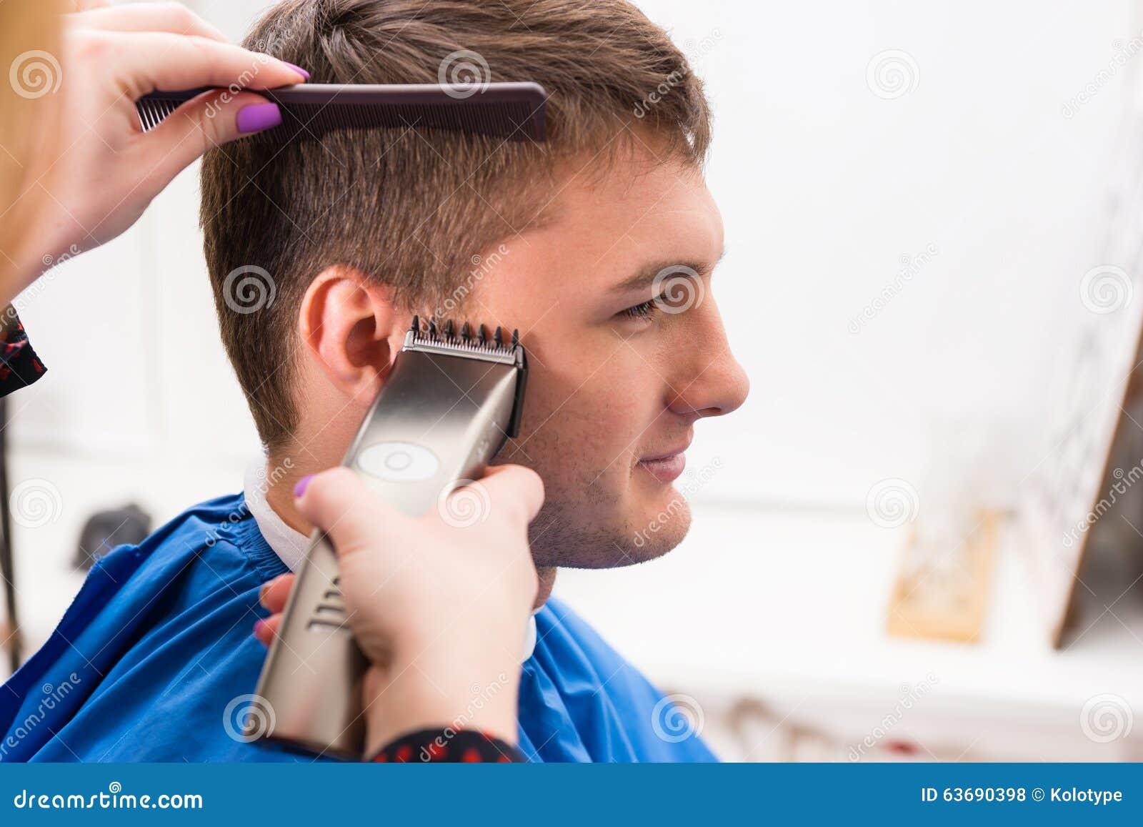 Mens die die Haar hebben door Stilist in Salon wordt gesneden