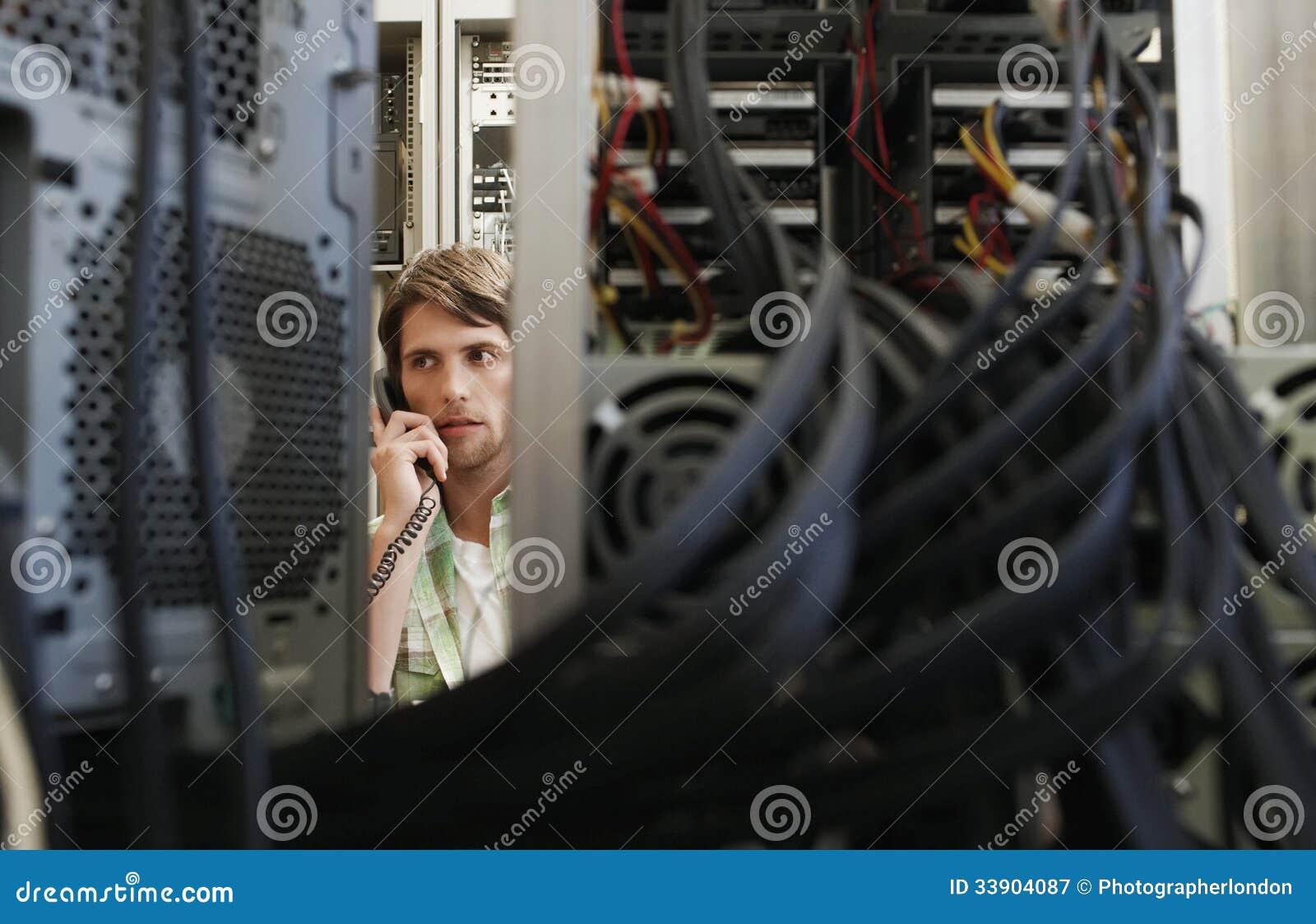 Mens die die Telefoon met behulp van door Computerapparatuur wordt omringd