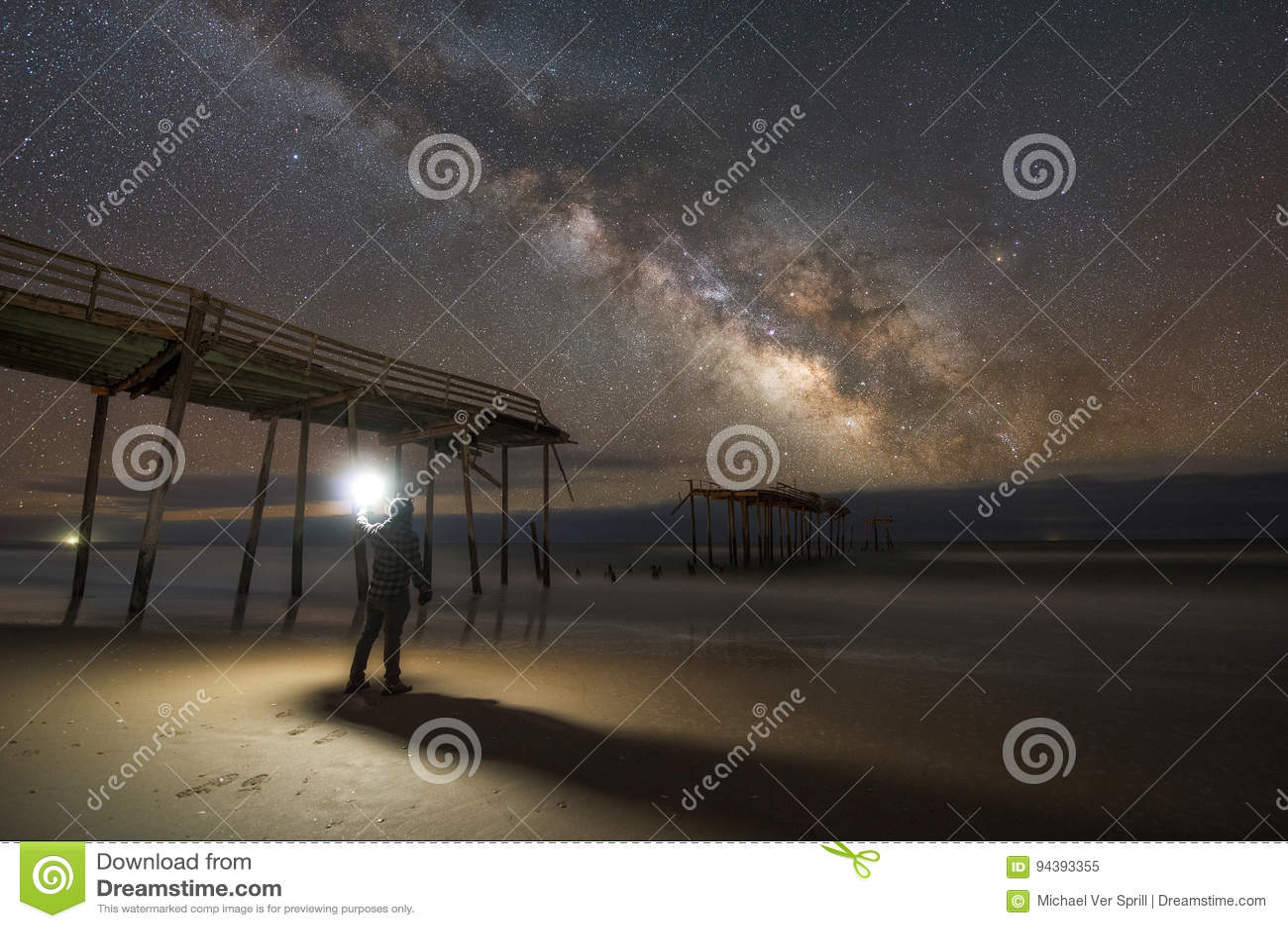 Mens die een beschadigde pijler onderzoekt bij nacht