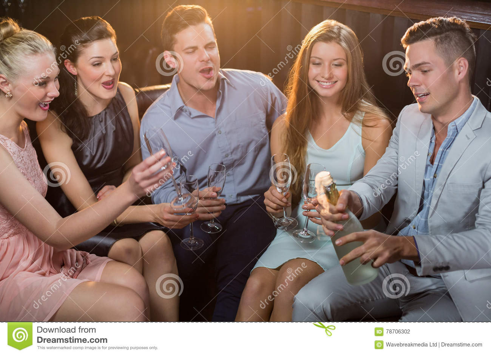 Mens die een champagnefles knallen terwijl vrienden die op hem letten