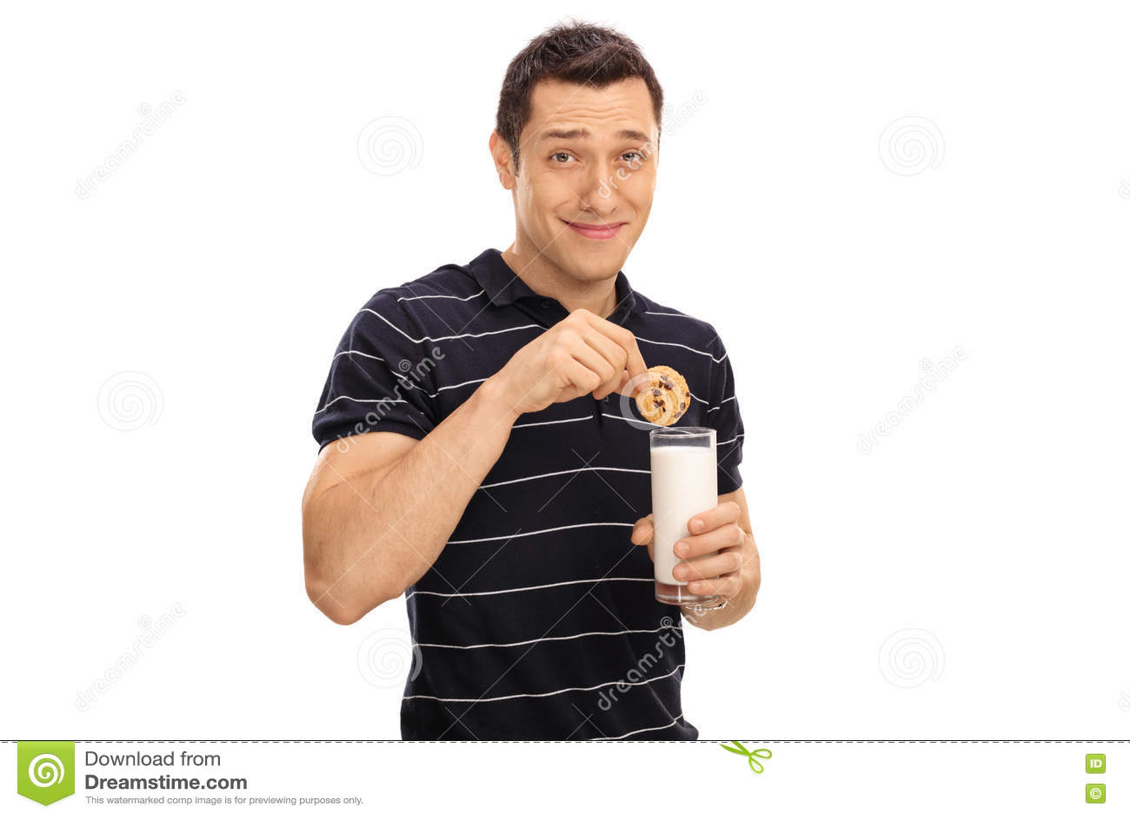Mens die een koekje in melk onderdompelen