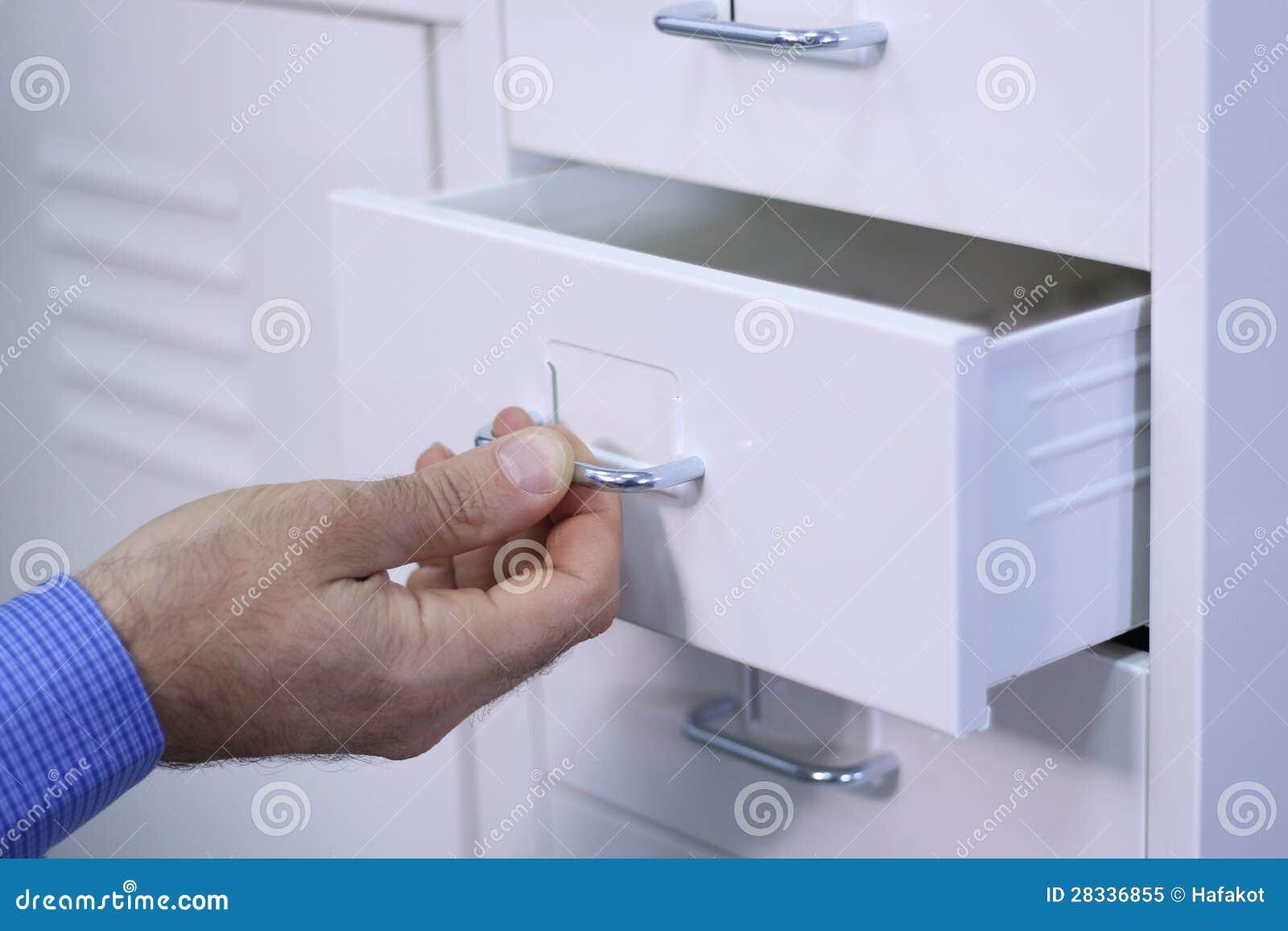 Mens die een lade in een kabinet openen