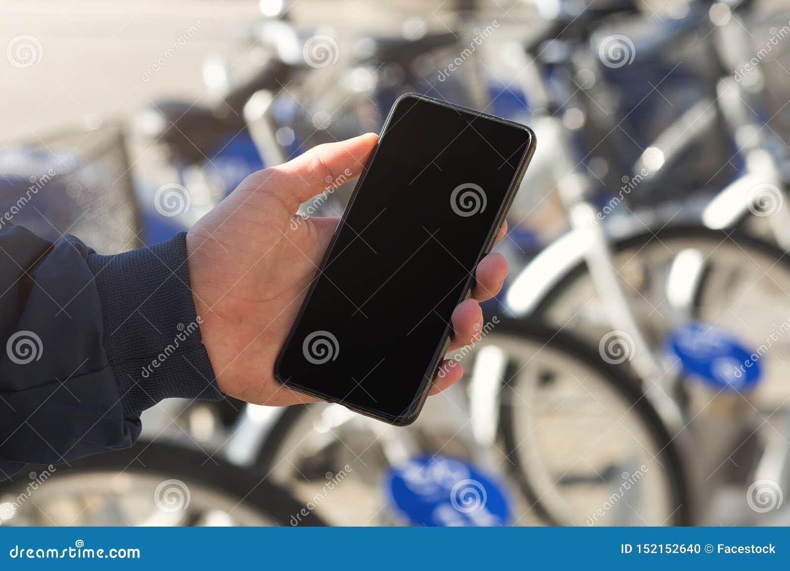 Mens die een mobiele telefoon voor fietspost met behulp van
