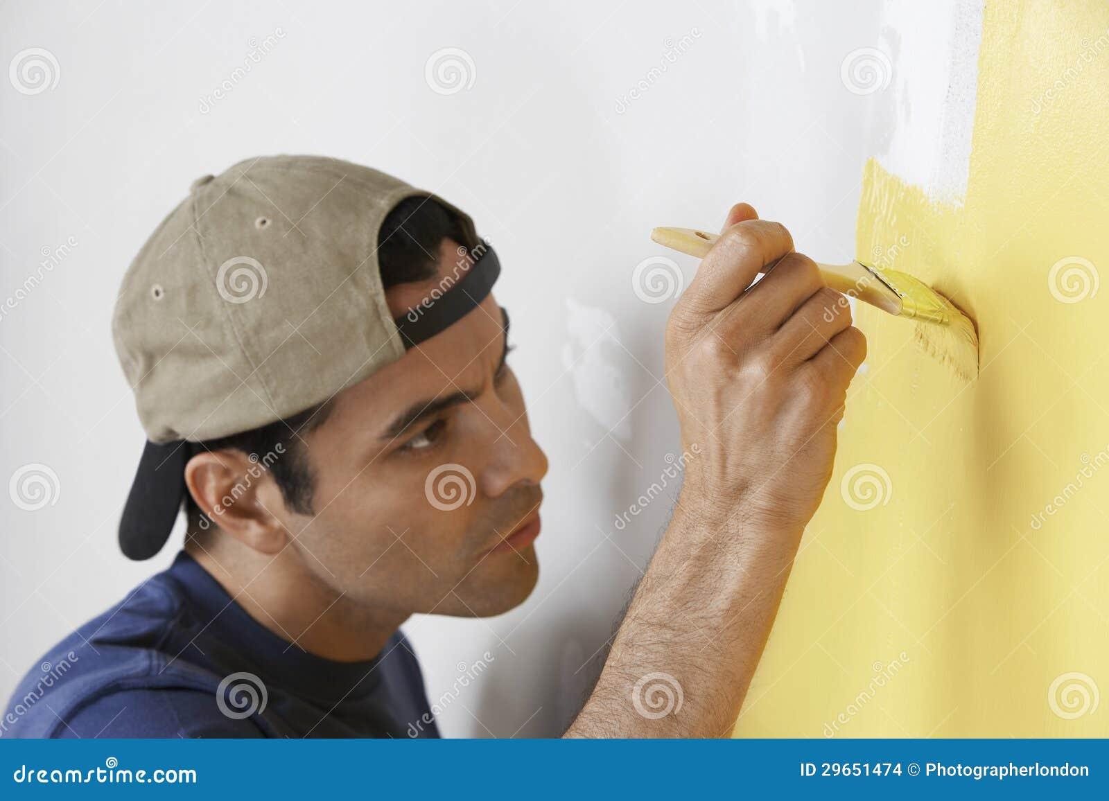 Mens die gele kleur op muur schilderen stock afbeeldingen ...