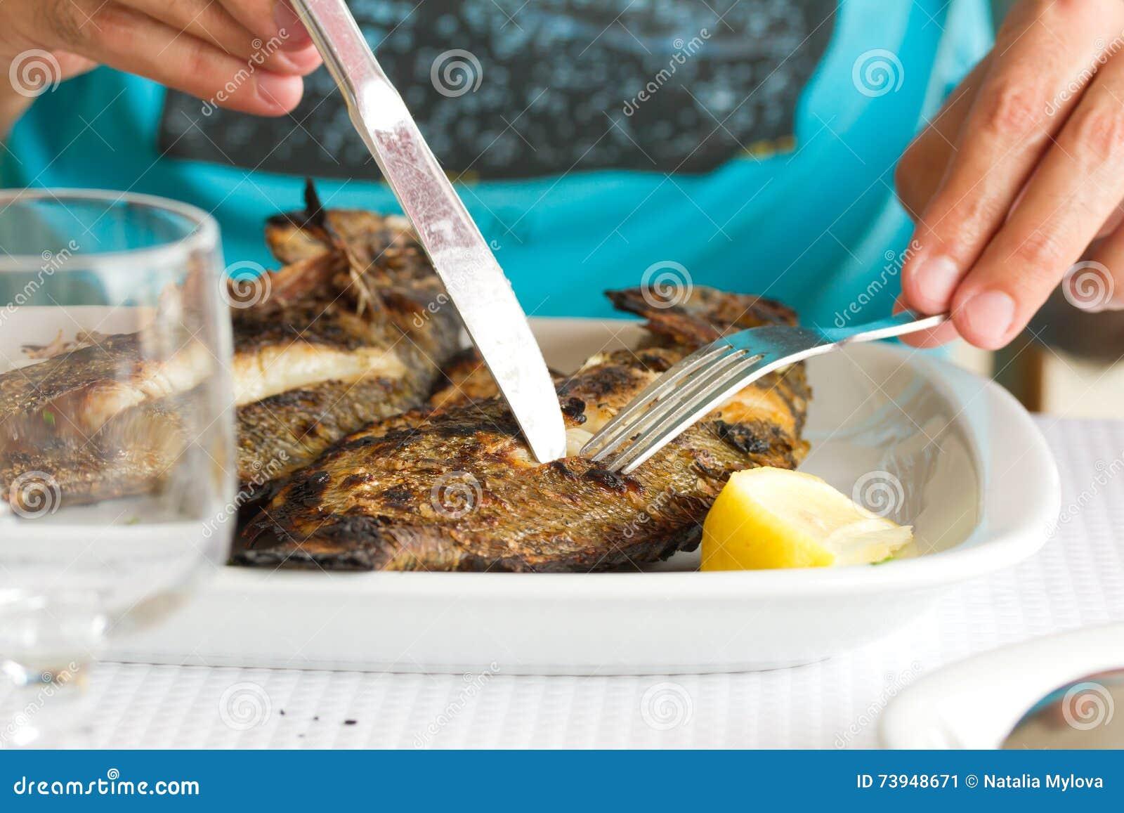 Mens die geroosterde vissen eten
