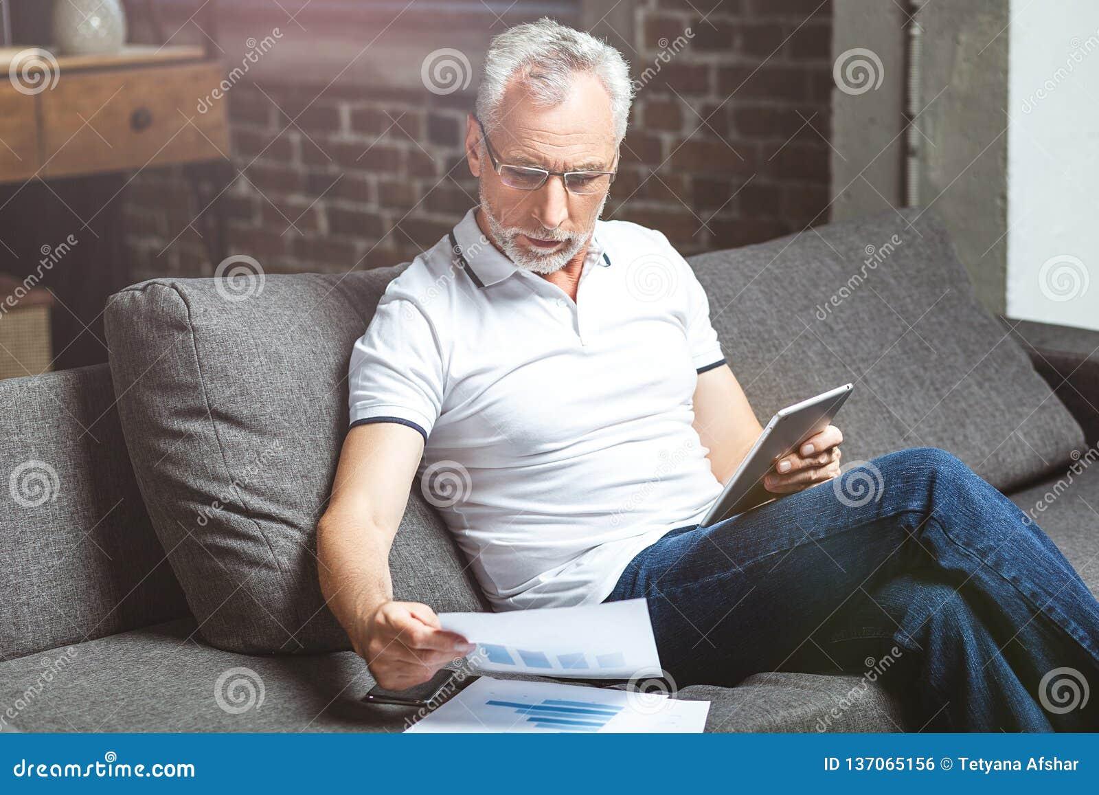 Mens die glazen dragen die op digitale tablet gebruiken