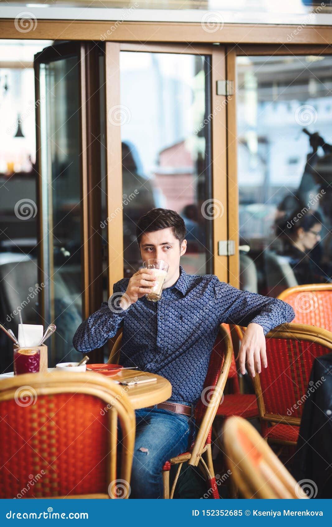 Mens die grote latte drinken bij een koffielijst