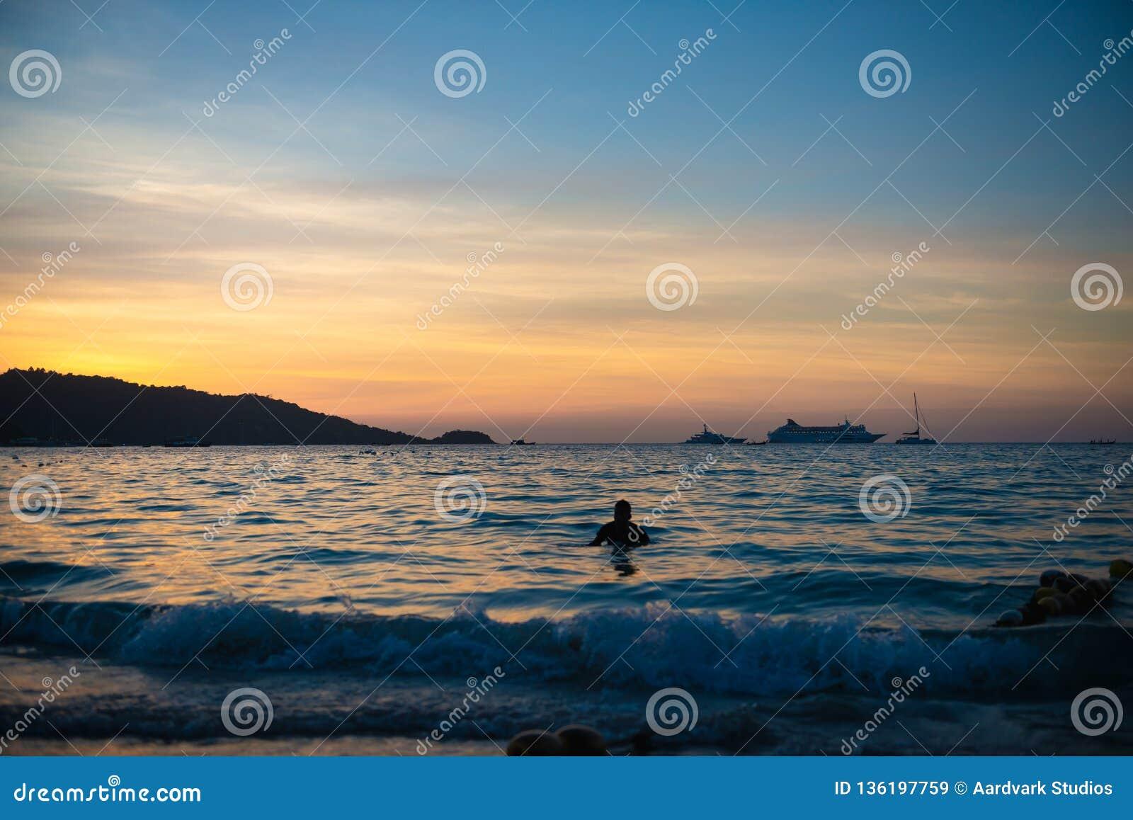 Mens die in het overzees na de zonsondergang zwemmen