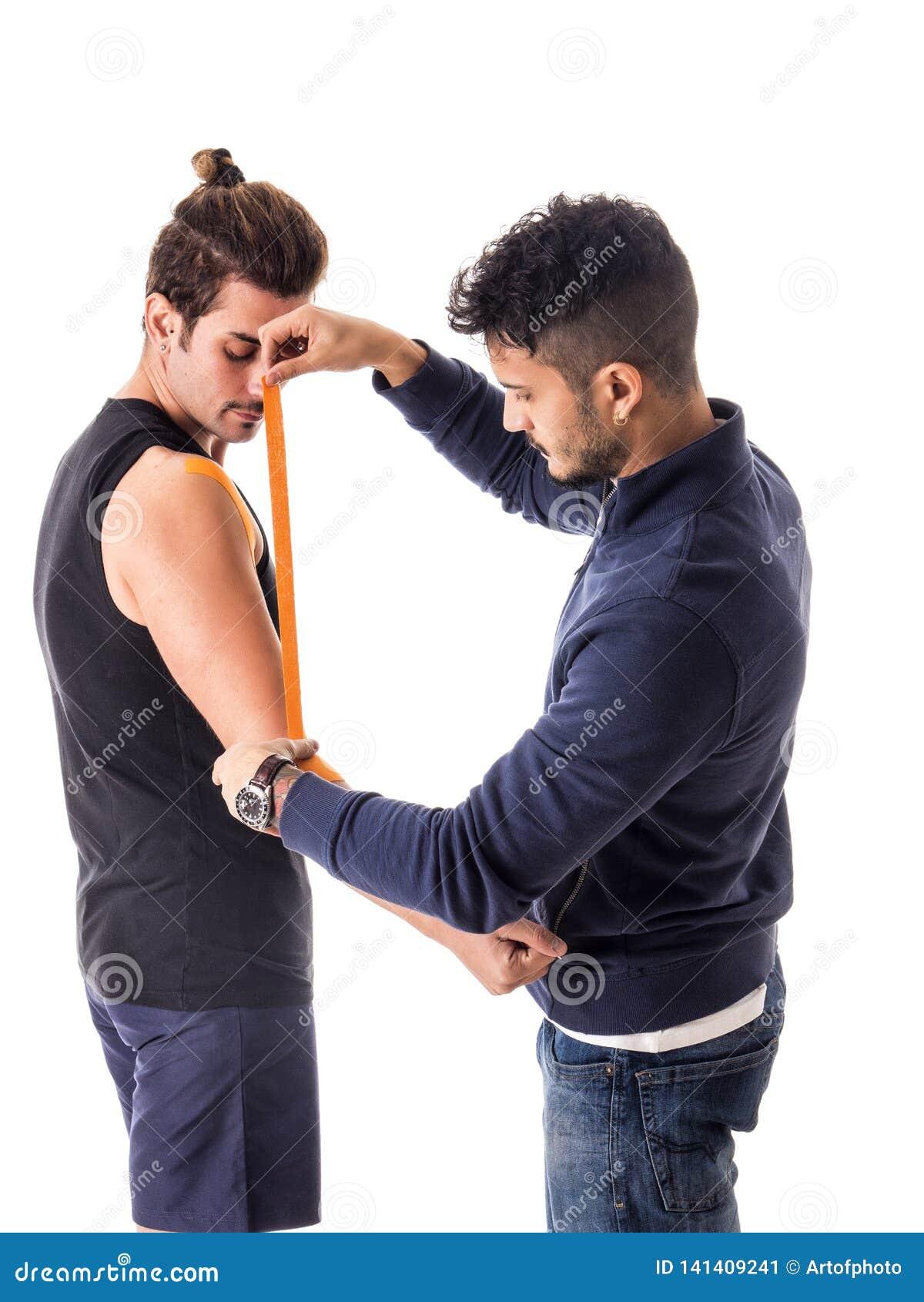 Mens die Kinesio-banden op wapens van sportman plakken