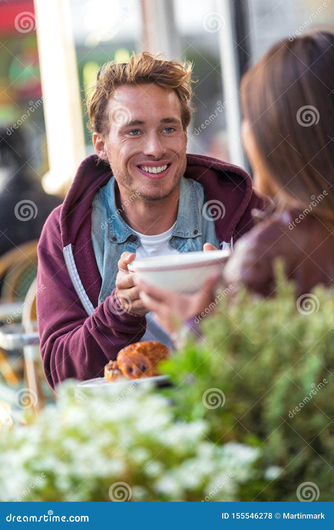 Mens die met meisje bij koffielijst spreken Vrienden die in stad samenkomen die pret het drinken koffie hebben Paar op een datum,