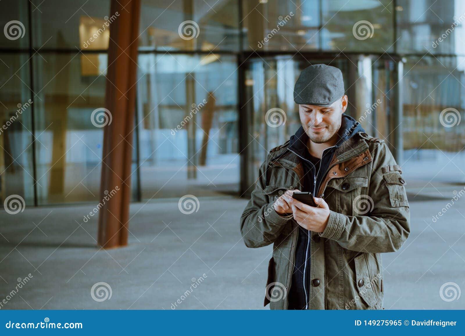 Mens die met zijn mobiele telefoon in zijn stedelijk leven communiceren Communicatie, technologie en levensstijlconcept