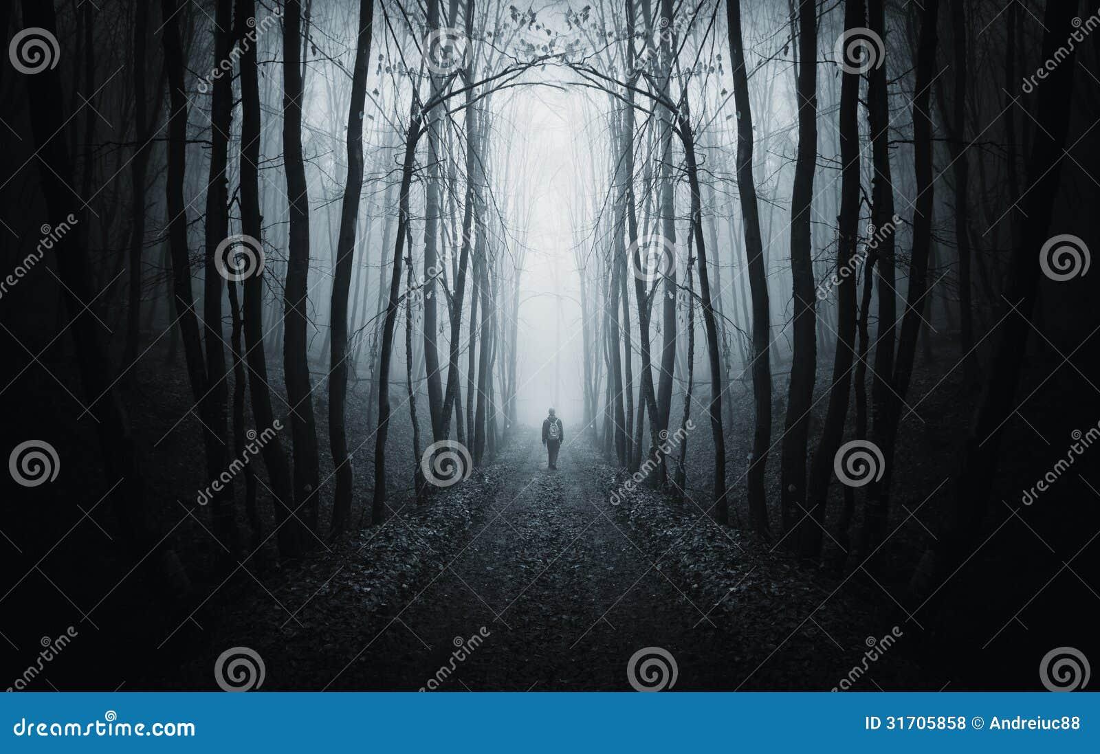 Mens die op een donkere weg in een vreemd donker bos met mist lopen