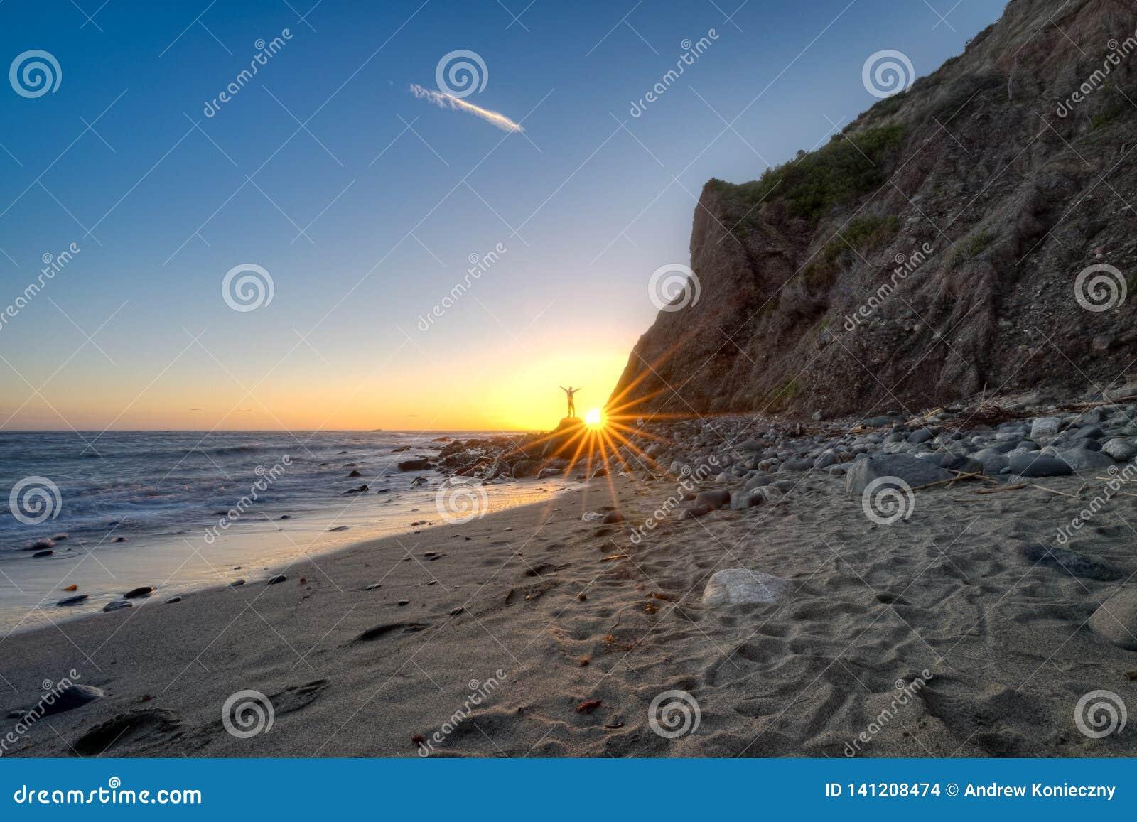 Mens die op een Rots bij Zonsondergang wordt gesteld