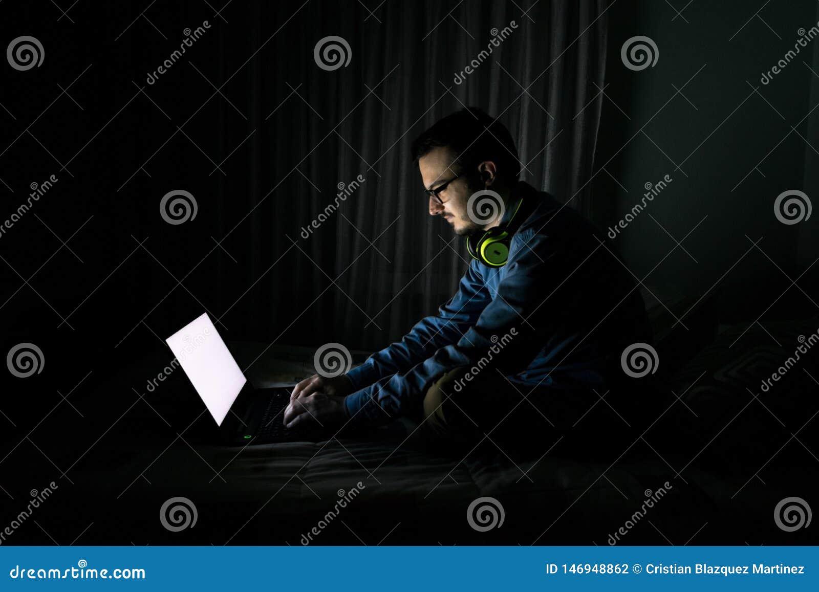 Mens die op TV in een laptop zitting op een bed in de nacht thuis letten
