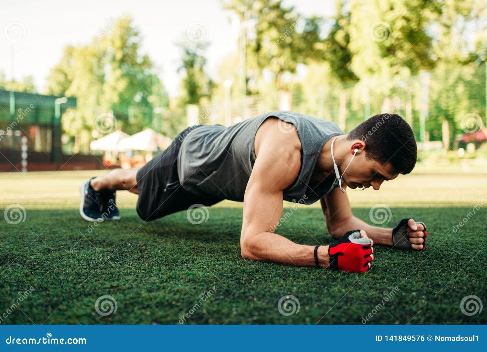 Mens die opdrukoefeningoefening op een gras doen openlucht
