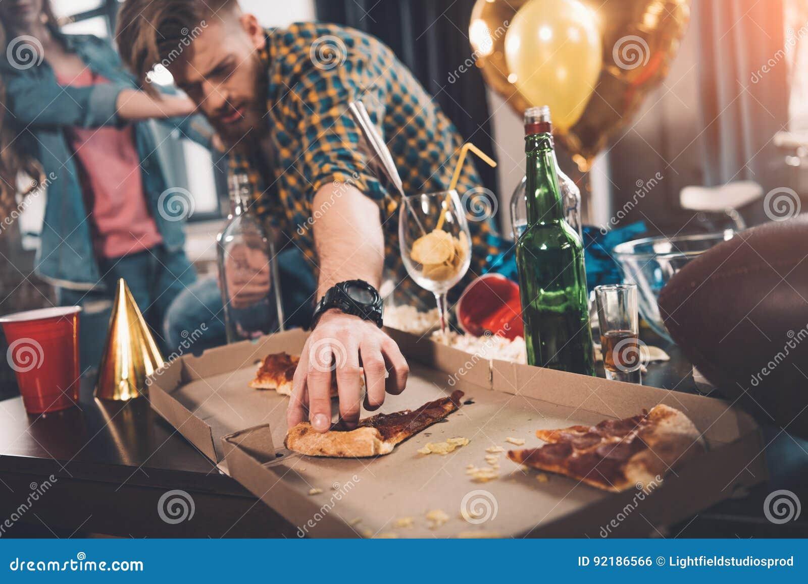 Mens die oude pizza in slordige ruimte eten