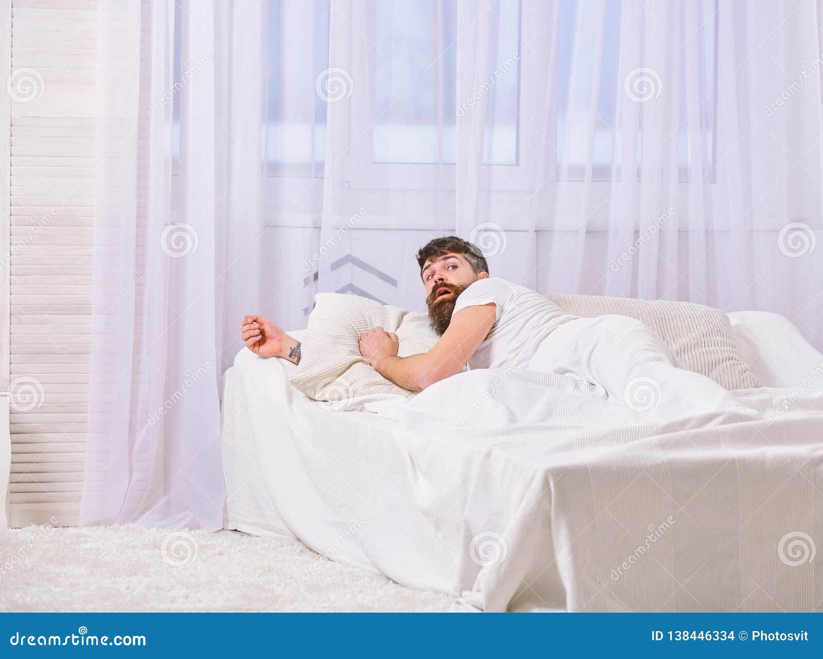 Mens die in overhemd op bed wakker, wit gordijn leggen op achtergrond Het kielzog omhoog en verslaapt zich concept Kerel op verra
