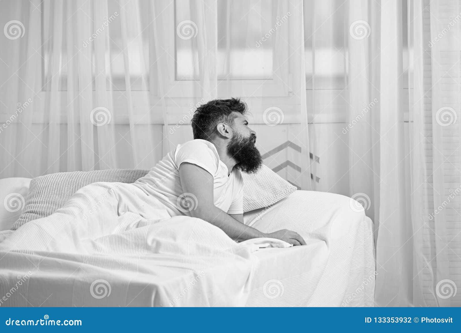Mens die in overhemd op bed wakker, wit gordijn leggen op achtergrond Katerconcept Kerel bij het teleurgestelde pijnlijke gezicht