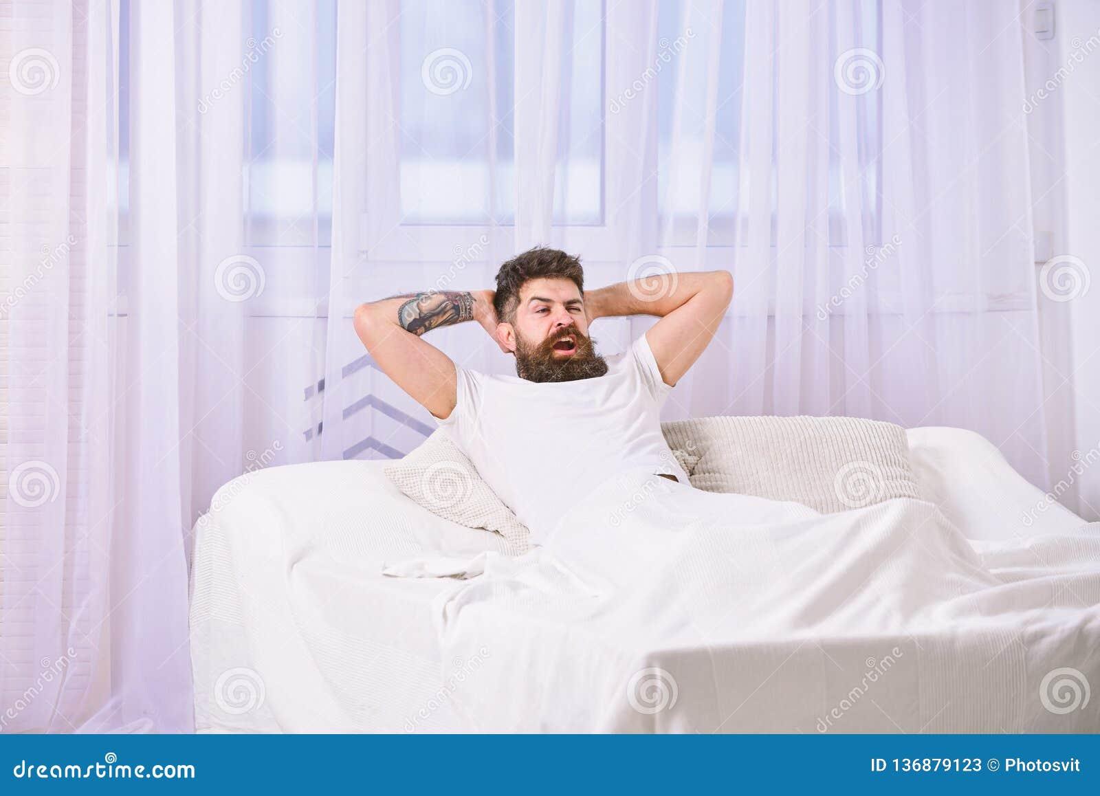 Mens die in overhemd op bed, witte gordijnen op achtergrond leggen Kerel op tevreden gezichtshoogtepunt van energie in ochtend Ho
