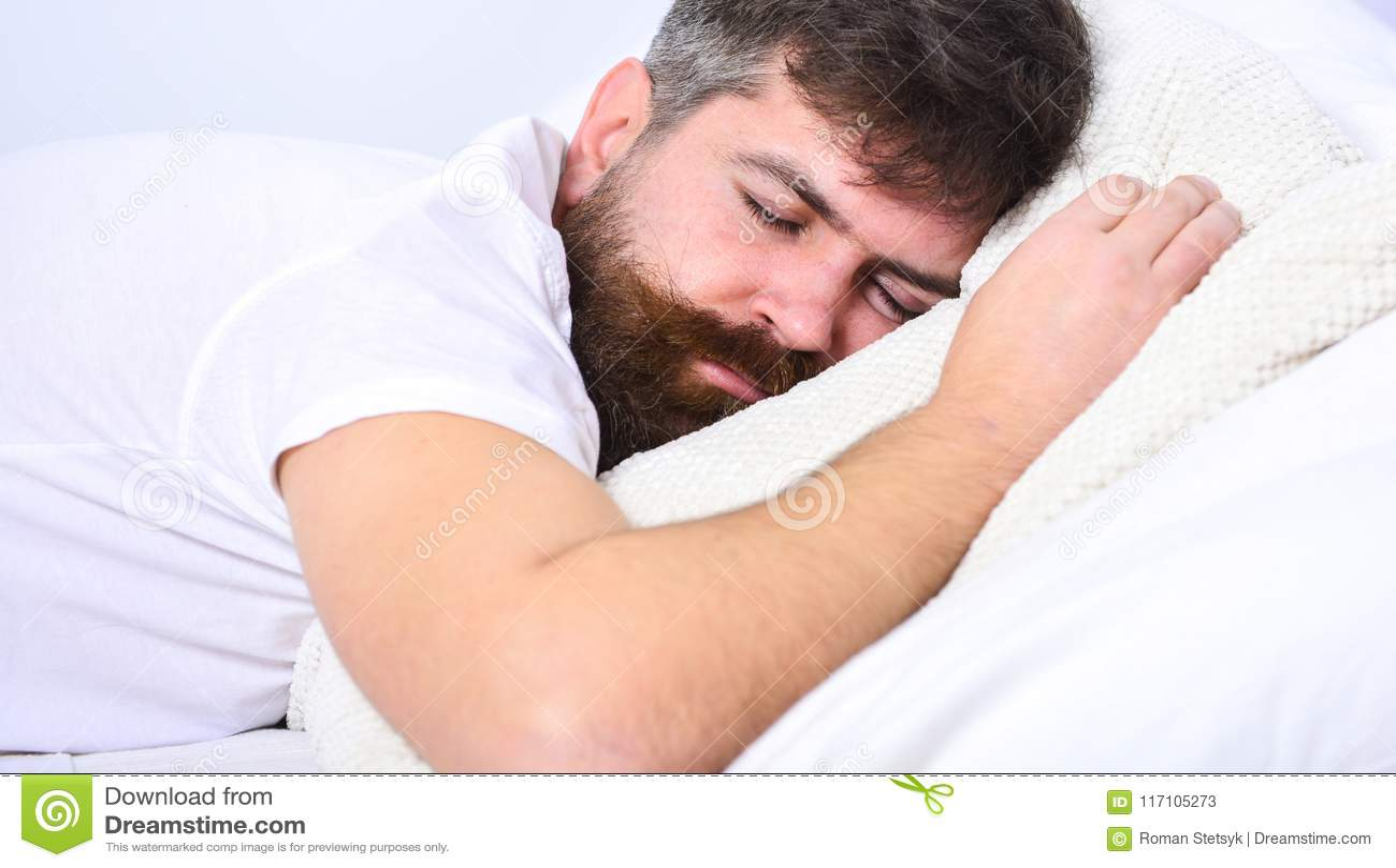 Mens die in overhemd op bed, witte muur op achtergrond leggen Macho met baard en snorslaap, die hebbend dutje, rust ontspannen