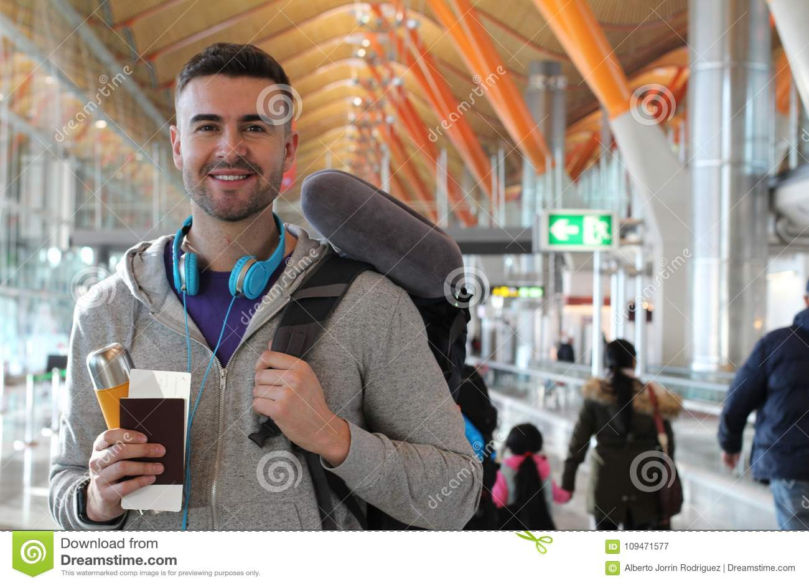 Mens die in overvolle luchthaven glimlachen