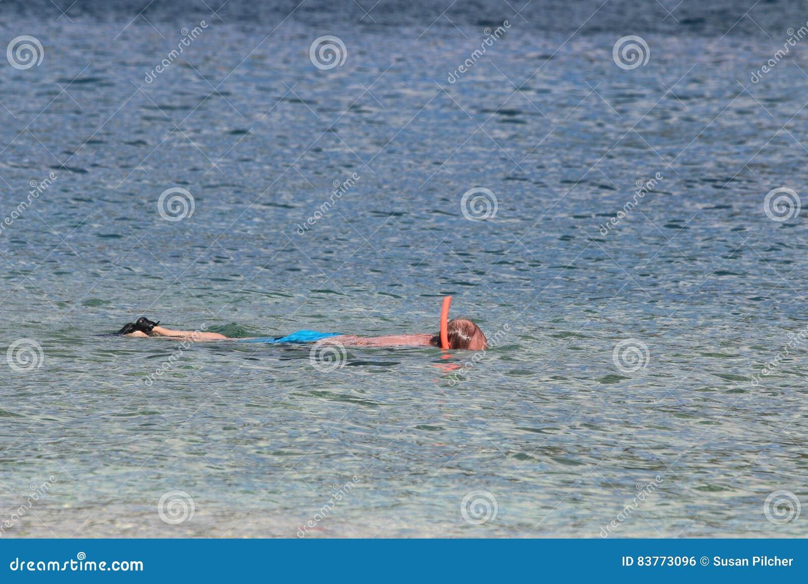 Mens die in overzees snorkelen die blauwe borrels dragen