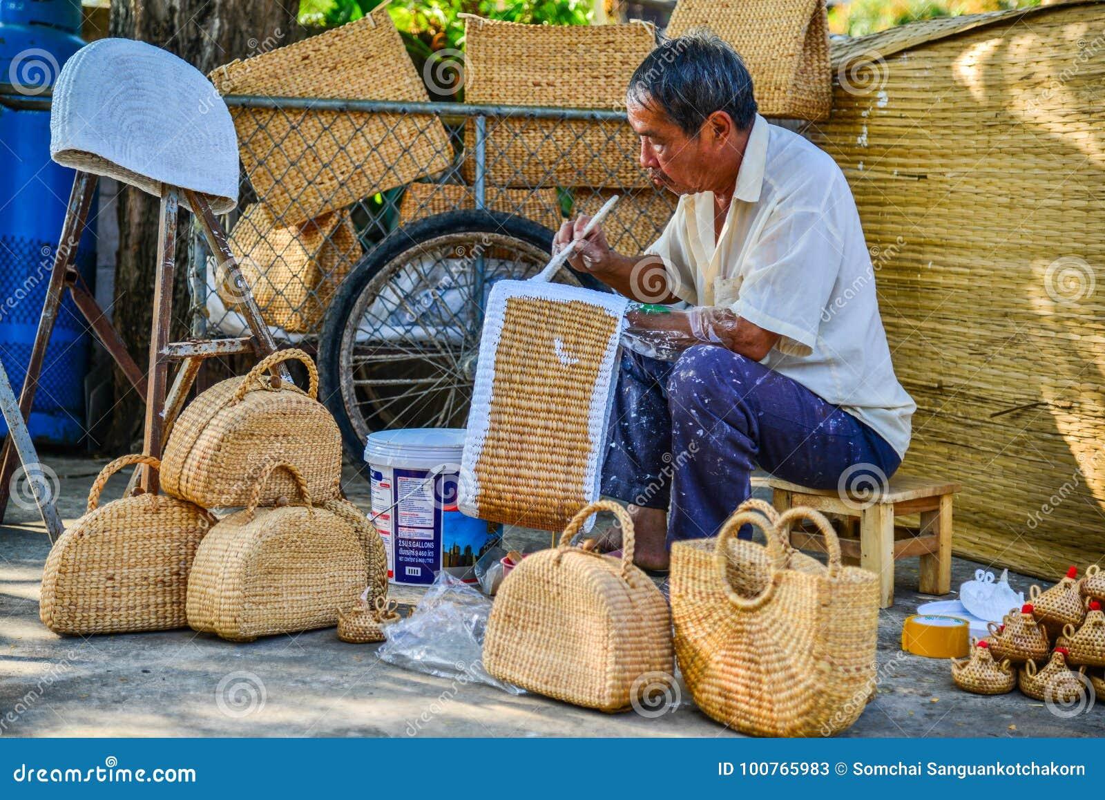 Mens die rieten handtas schilderen