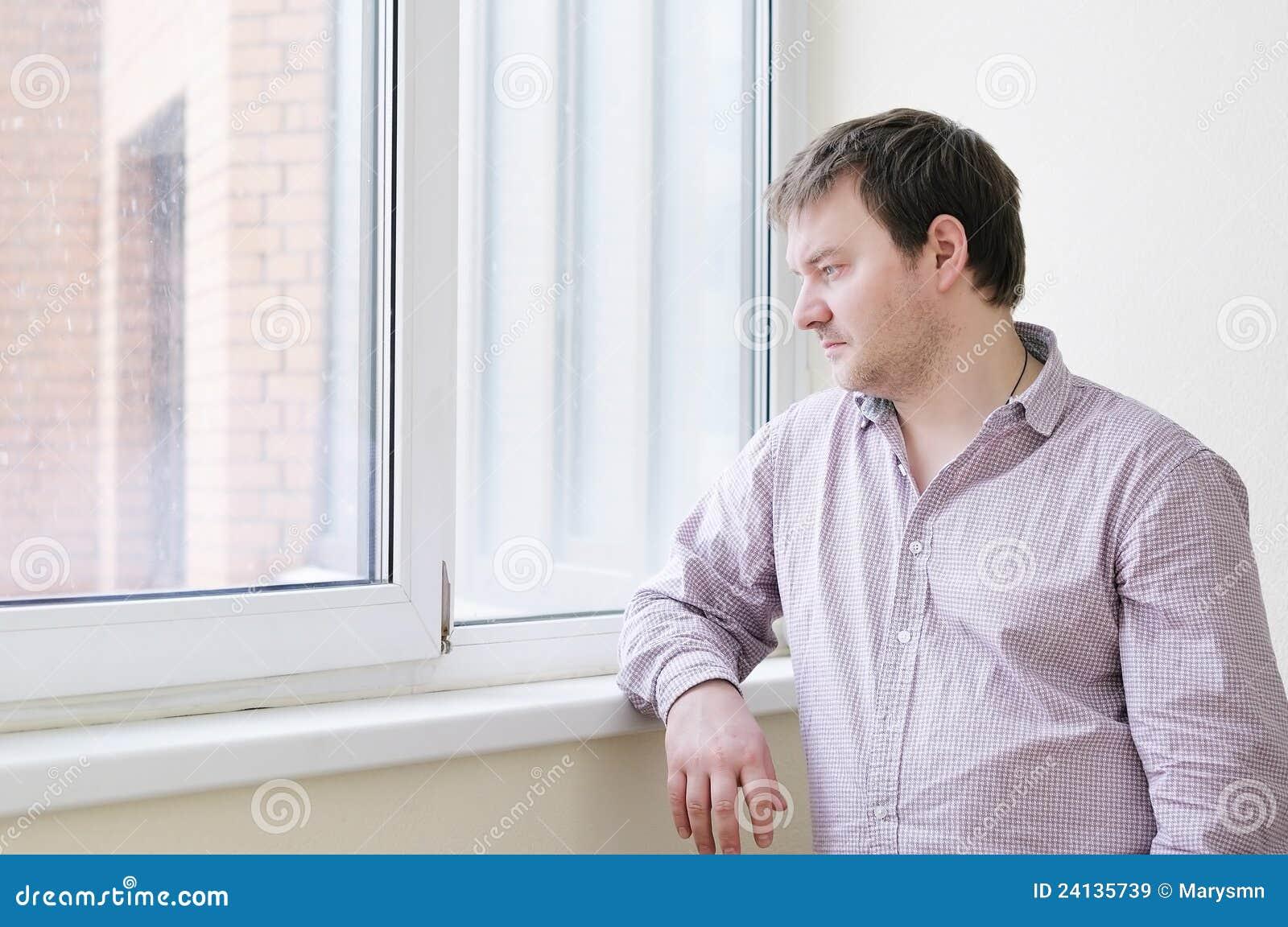 Mens die sneeuw in het venster bekijkt