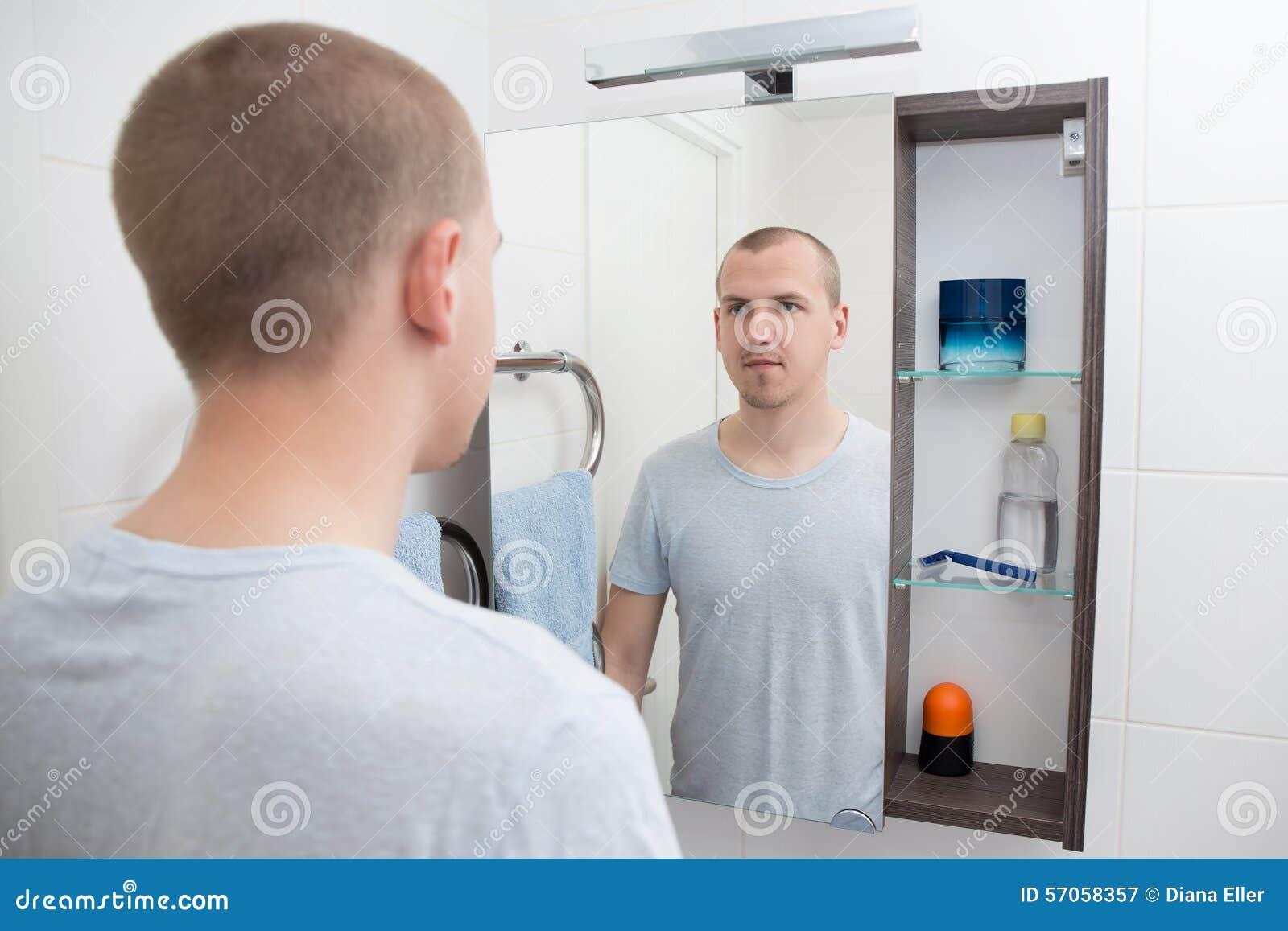 Mens die spiegel in badkamers bekijken
