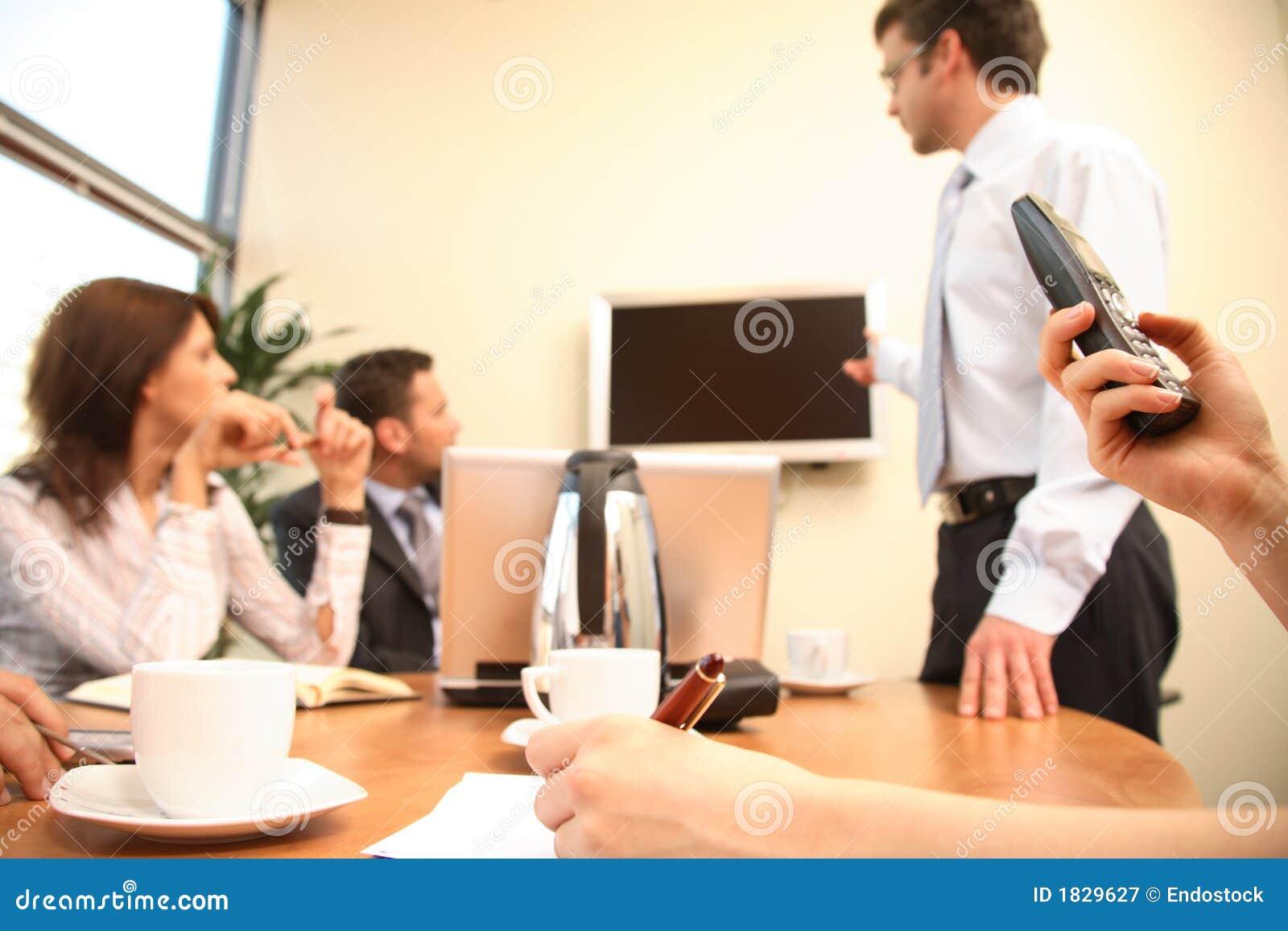Mens die tot presentatie op het scherm van TV maakt aan de groep mensen