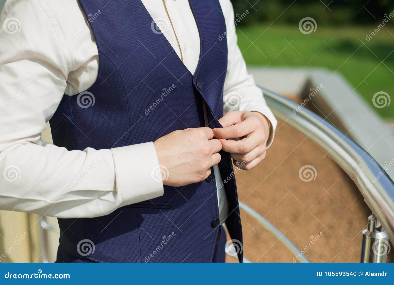 Mens die vest van blauw kostuum dichtknopen