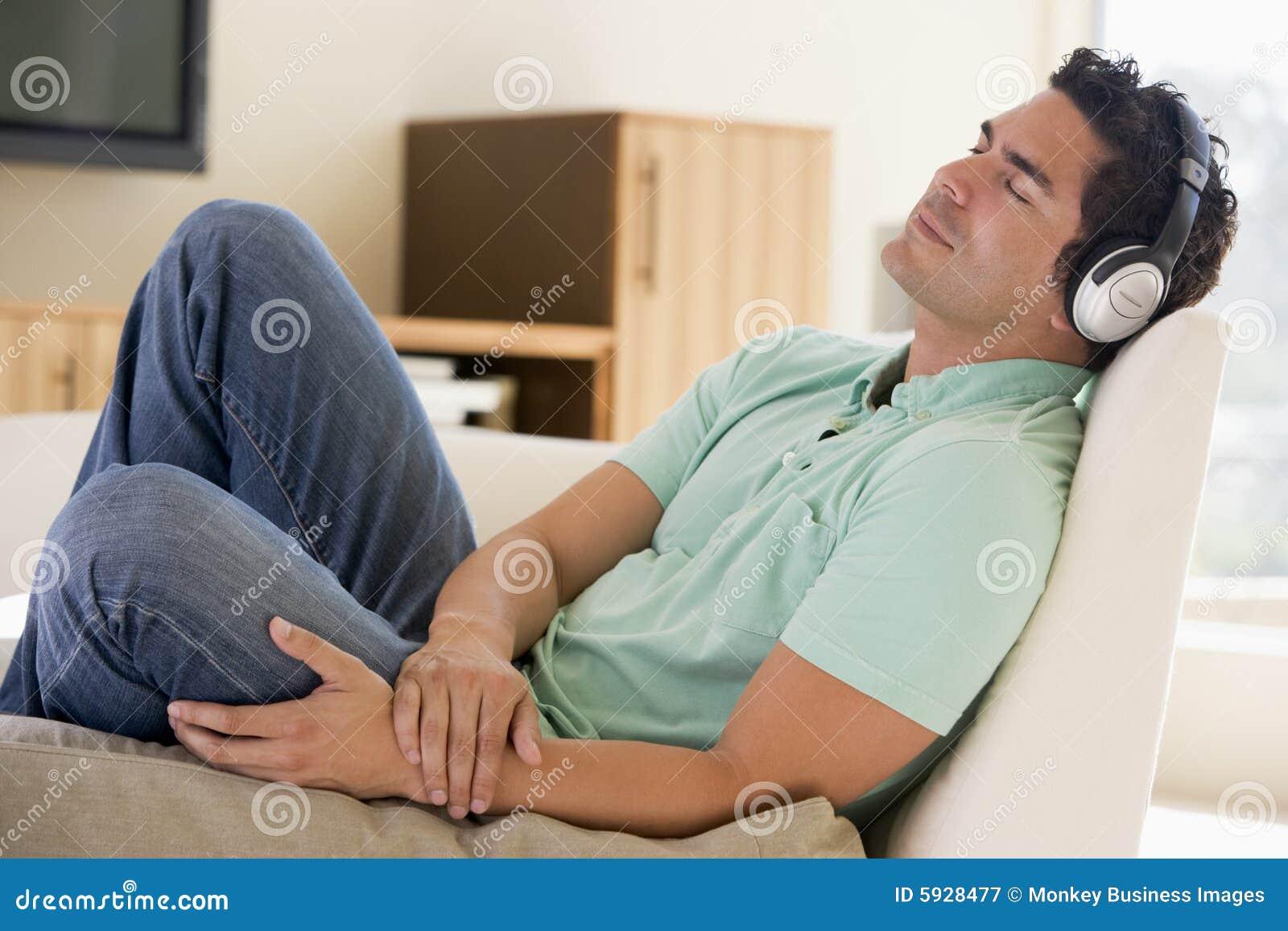 Mens die in woonkamer aan hoofdtelefoons luistert