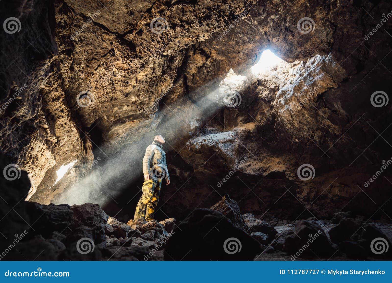 Mens die zich onder het licht in het berghol bevinden Extreme avonturenreis concep
