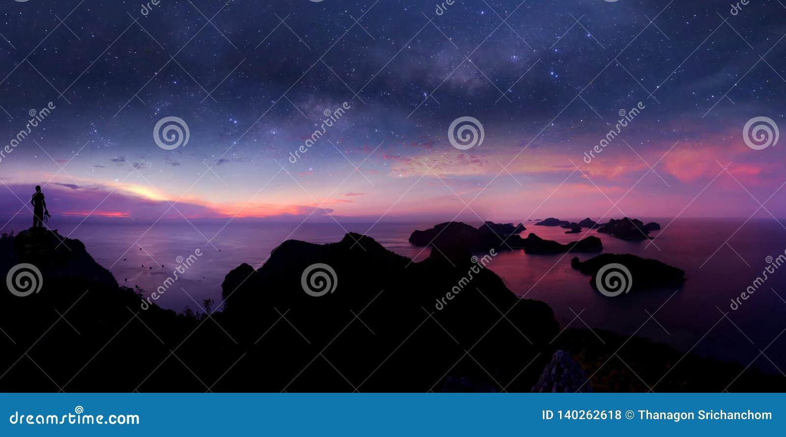Mens die zich op de berg met panoramamening en miljoen sterrenmelkweg bevinden