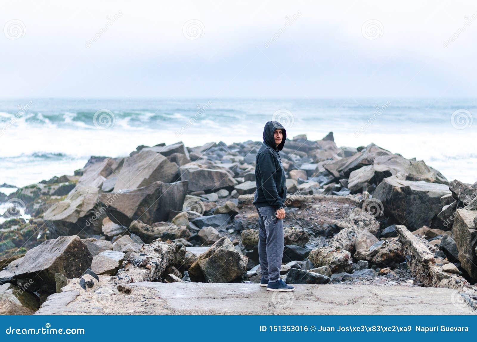 Mens die zich op de rots in het midden van de oceaan bevinden