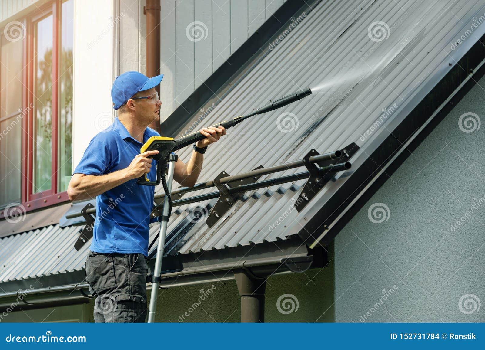 Mens die zich op ladder en het schoonmakende dak van het huismetaal met hoge drukwasmachine bevinden