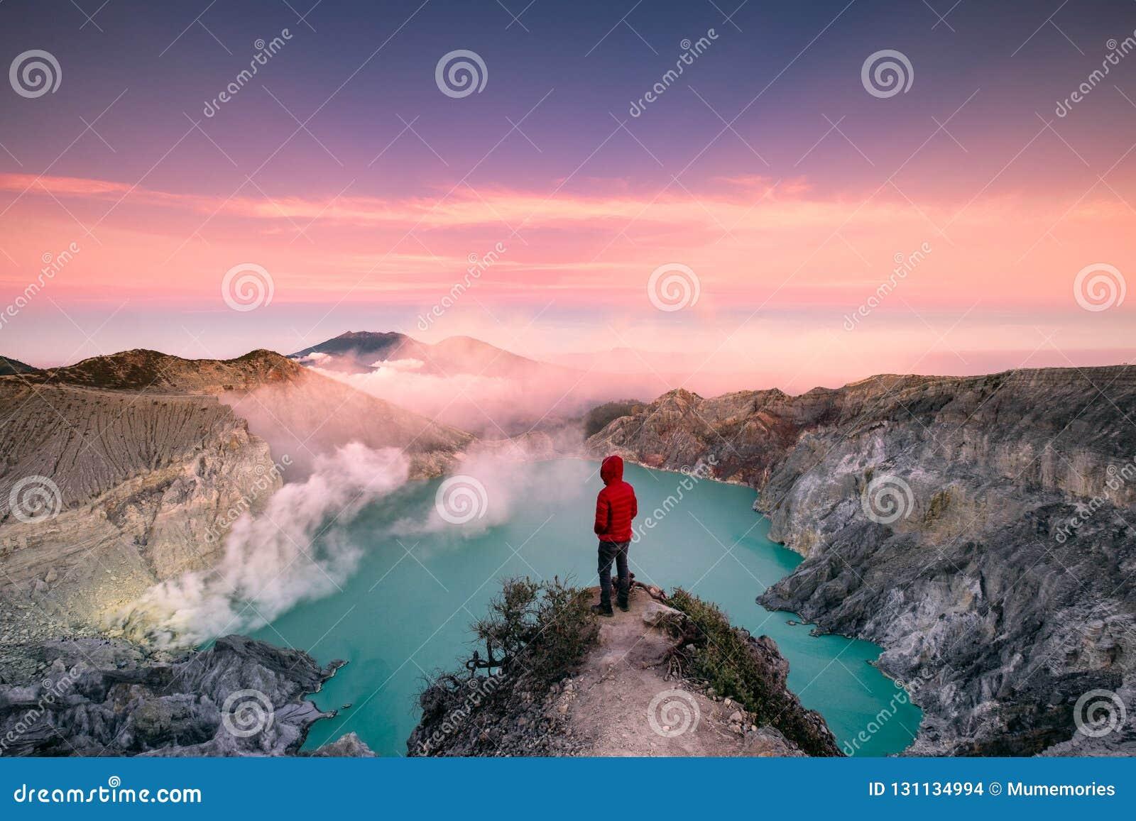 Mens die zich op rand van krater met kleurrijke hemel bij ochtend bevinden