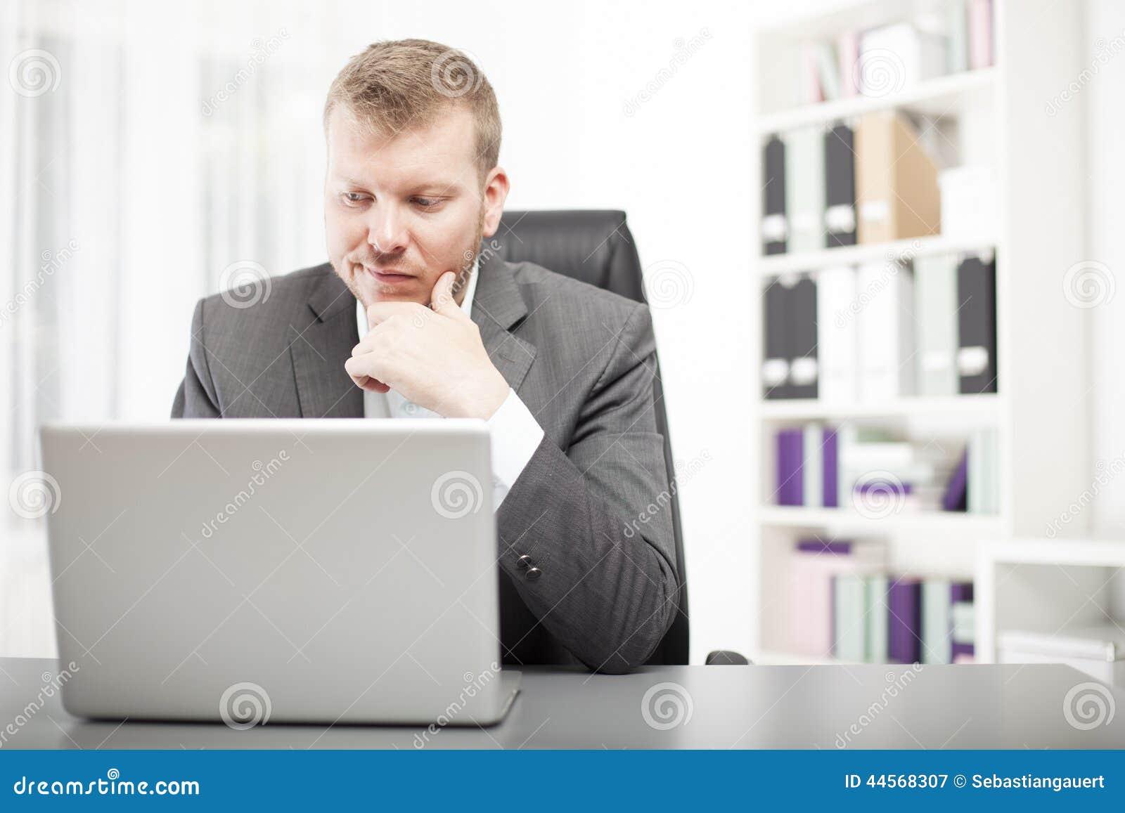 Mens die zijn laptop met een gedwongen uitdrukking bekijken