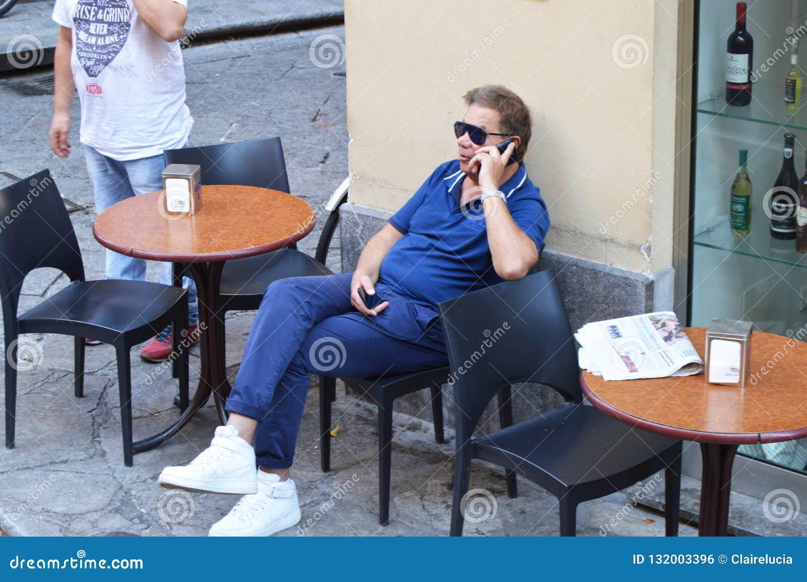Mens die in zonnebril in openluchtkoffie zitten die van vrije tijd genieten die op mobiele telefoon, Italië, Sicilië, Palermo, 8