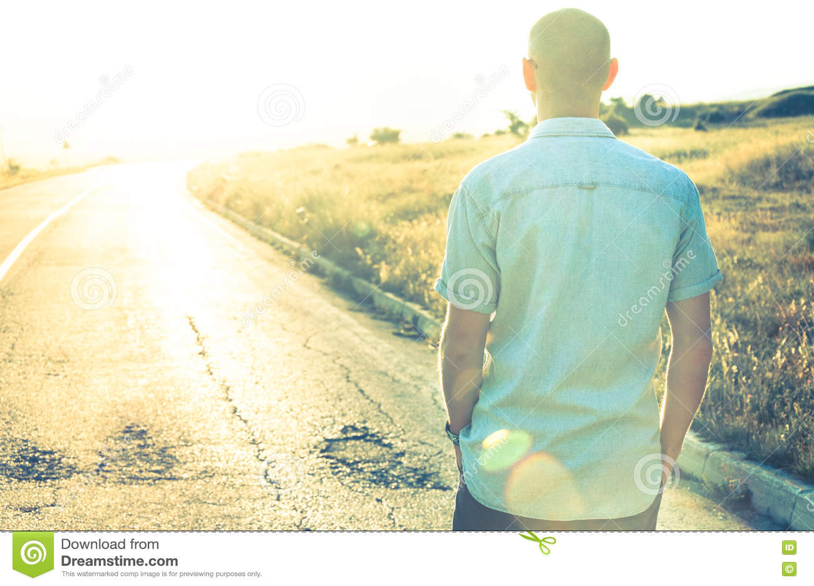 Mens die in zonsondergang op lege weg lopen