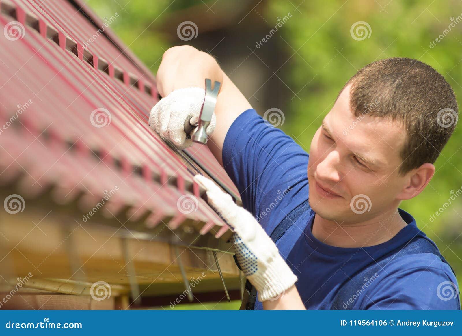 Mens in een blauw kostuum die het dak van het huis, close-up herstellen