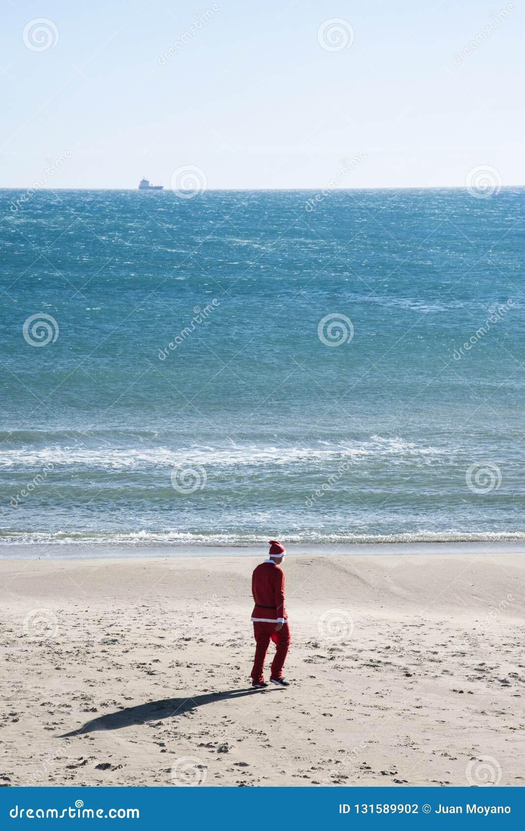 Mens in een santakostuum die op het zand van een strand lopen