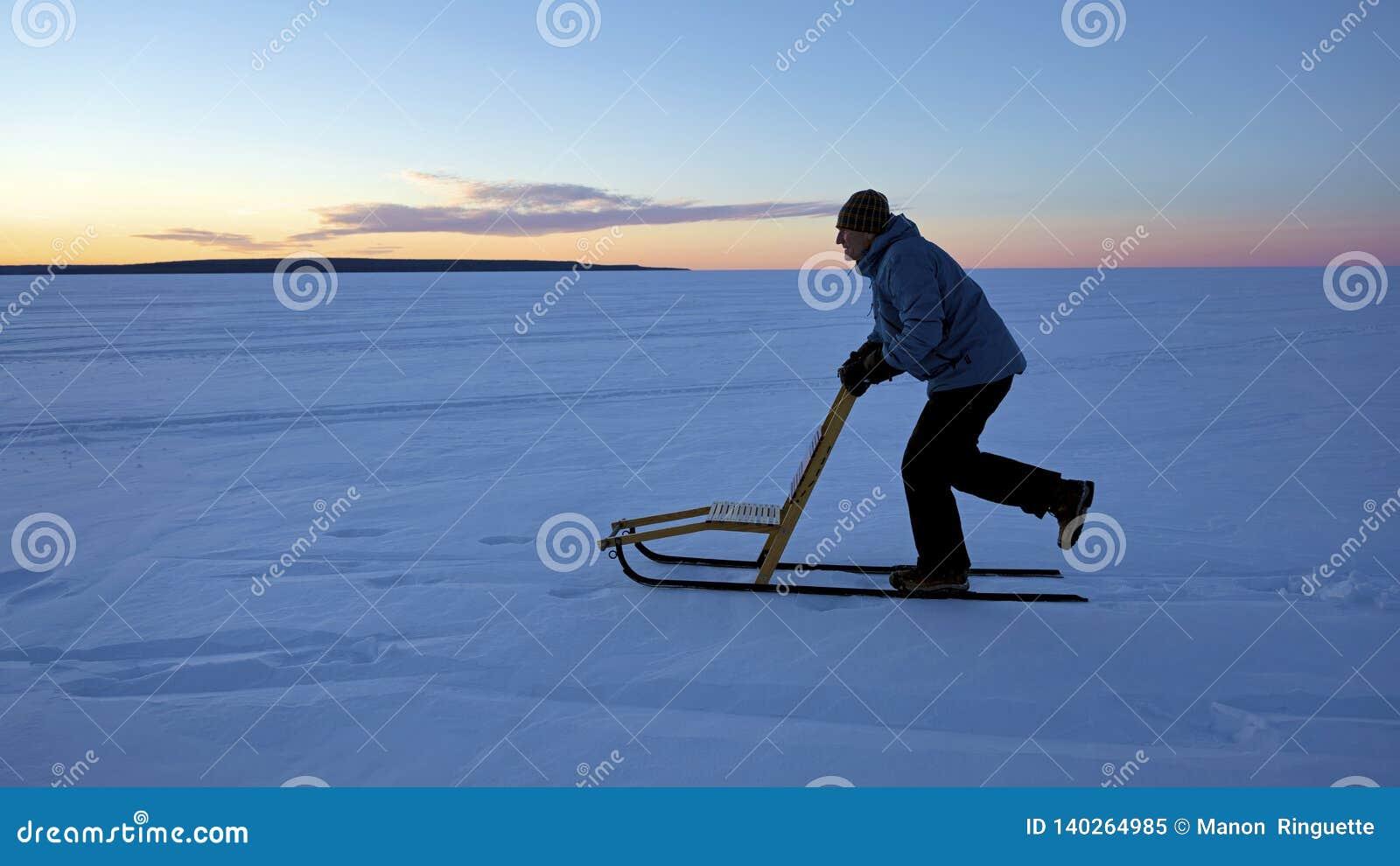 Mens geschikt het kicksledding om tijdens wintermaanden te blijven