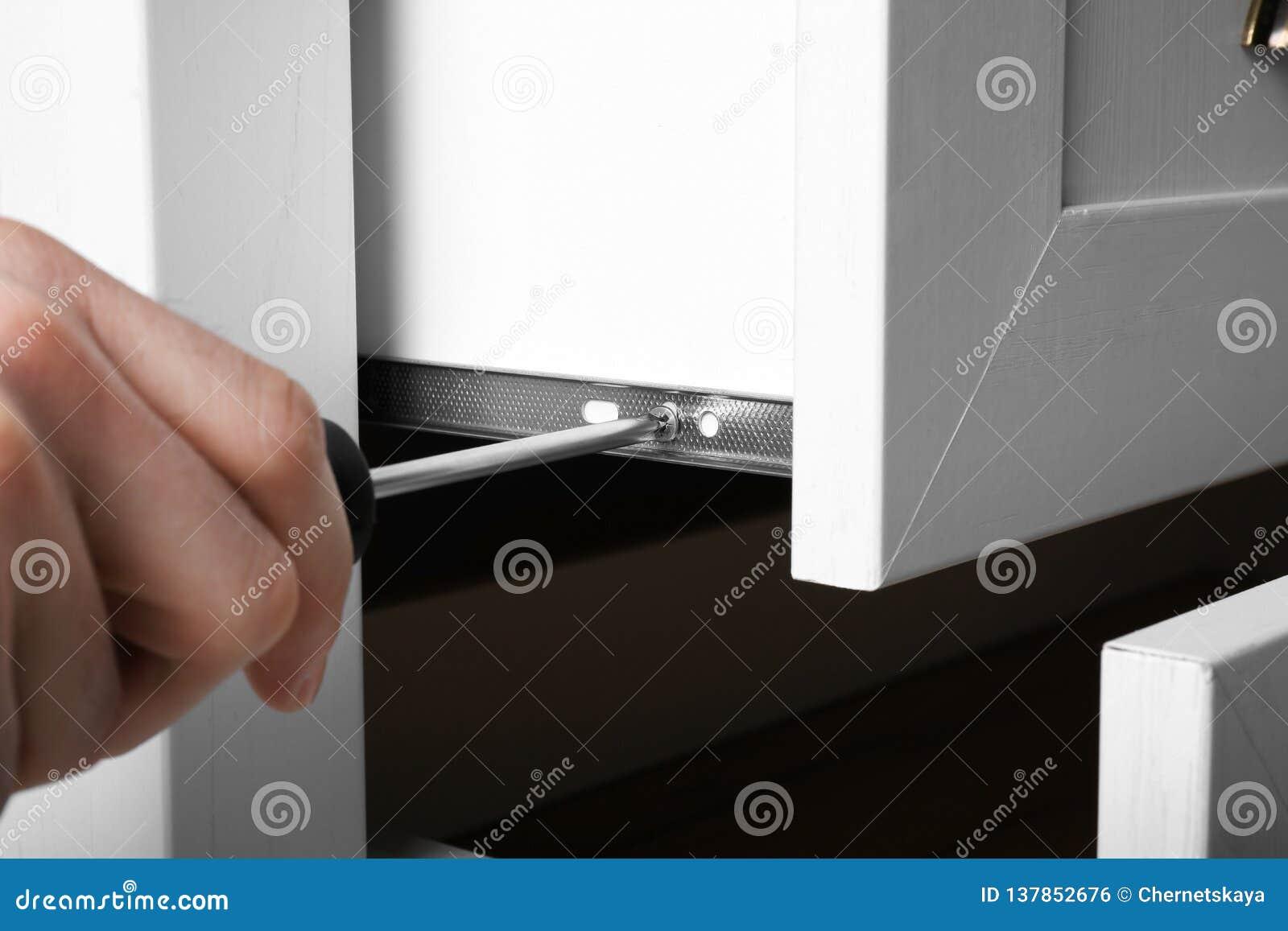 Mens het bevestigen lade van witte garderobe met schroevedraaier