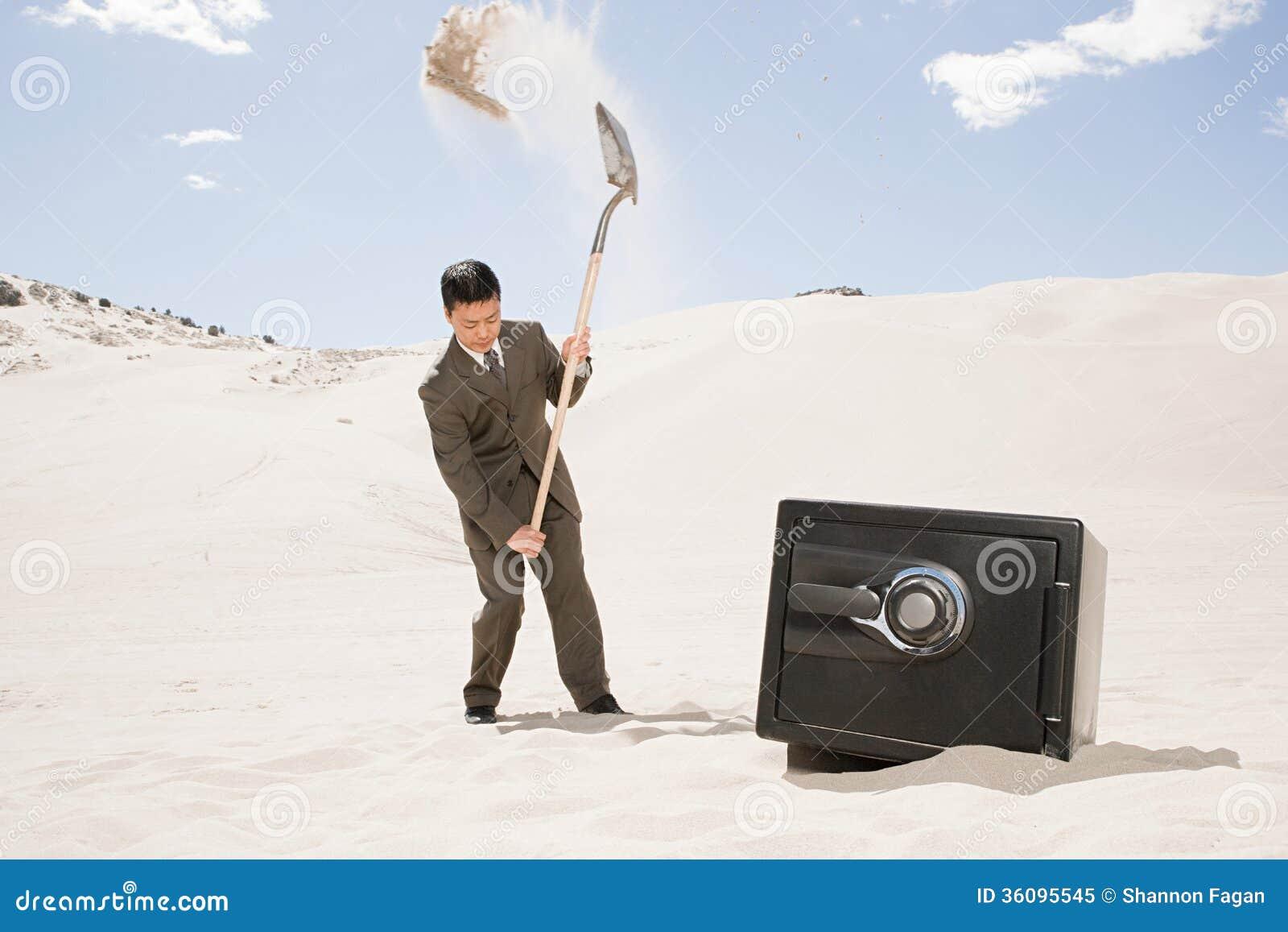 Mens het graven door brandkast in woestijn